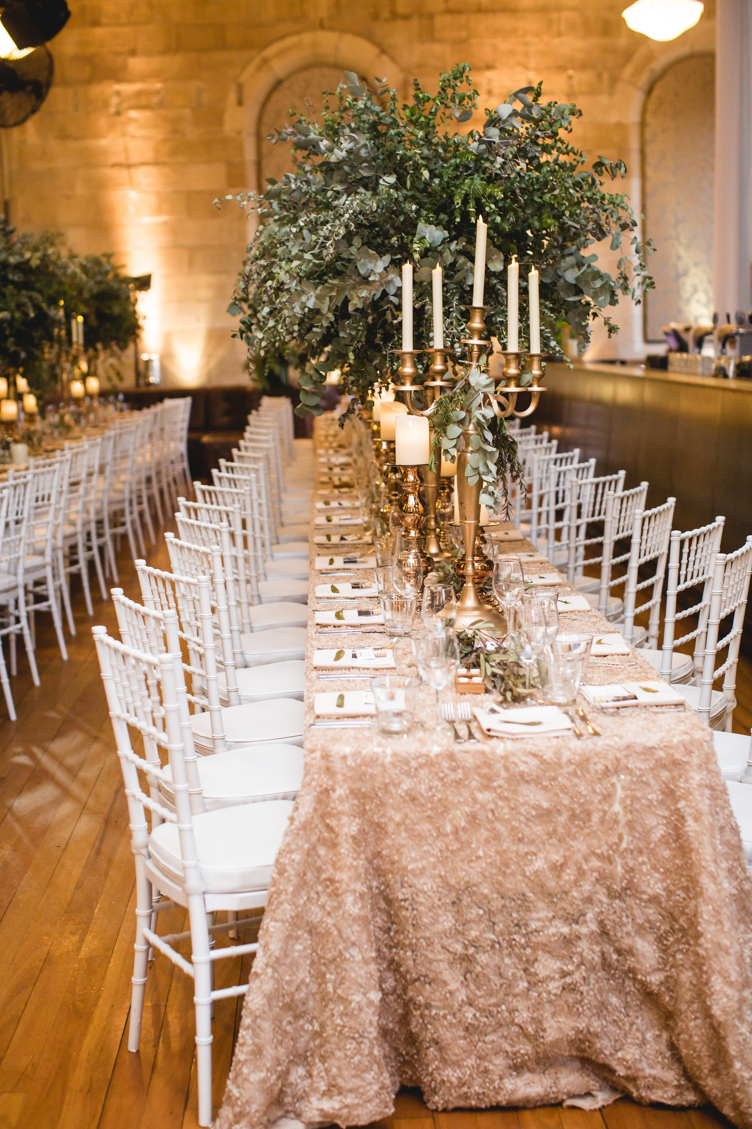 Columbine and Damien - Champagne Heather luxury linen, gold Stefania candlesticks with LED pillar candles, gold 5 arm candelabra, tree centrepiece, white Tiffany chairs 2.jpg