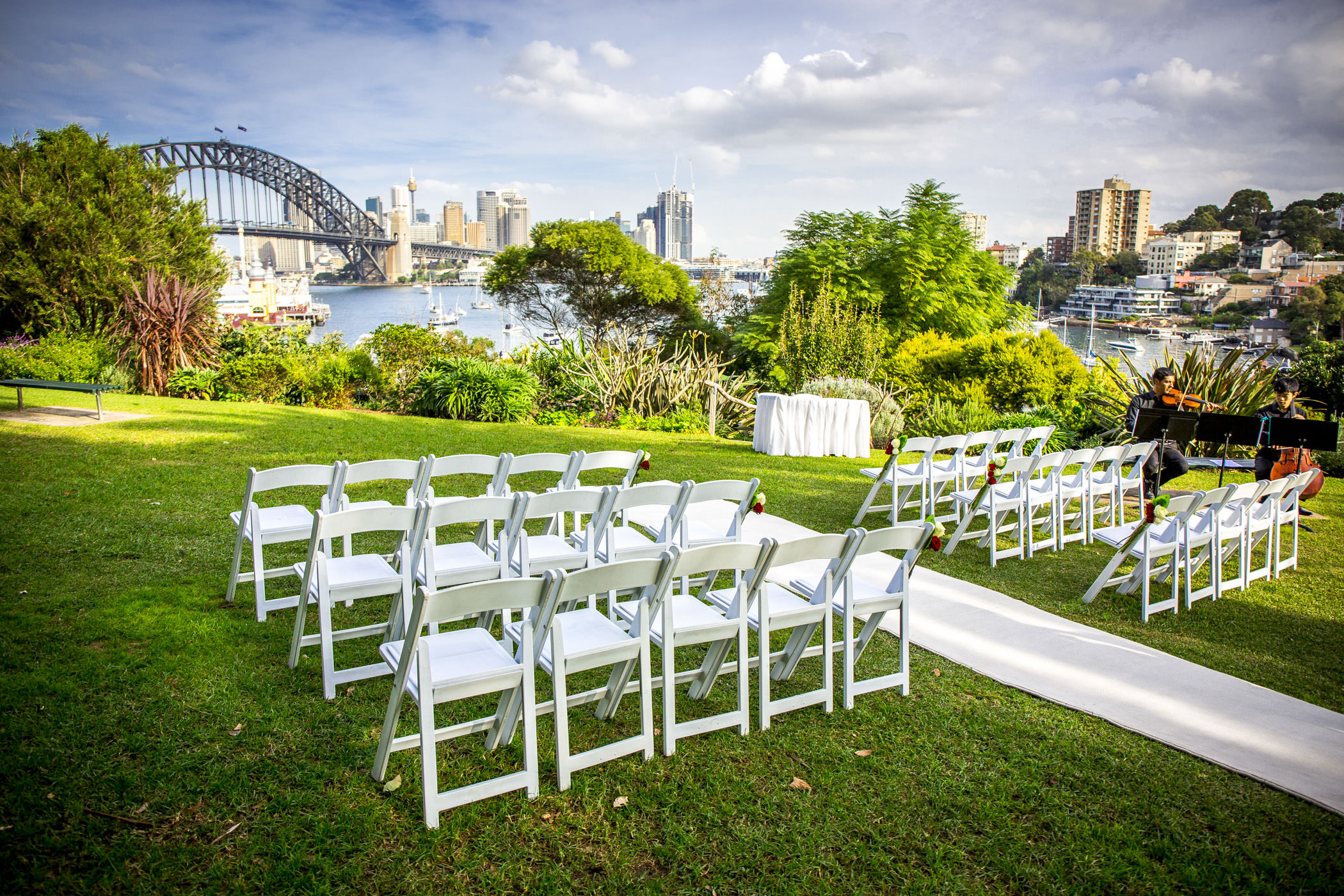 Clark Park ceremony - White carpet, signing table with white cloth, fold up padded chairs and red and white roses pew ends.jpg