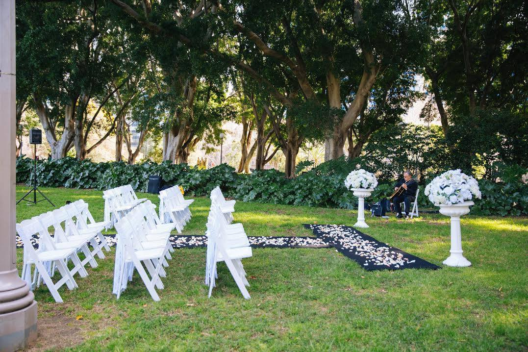 Hyde Park - Ceremony, black carpet, set up as a T, scattered rose petals, white folding chairs with white lace chair sashes and a set of 2 victorian urns with silk flowers - Image 1.jpg