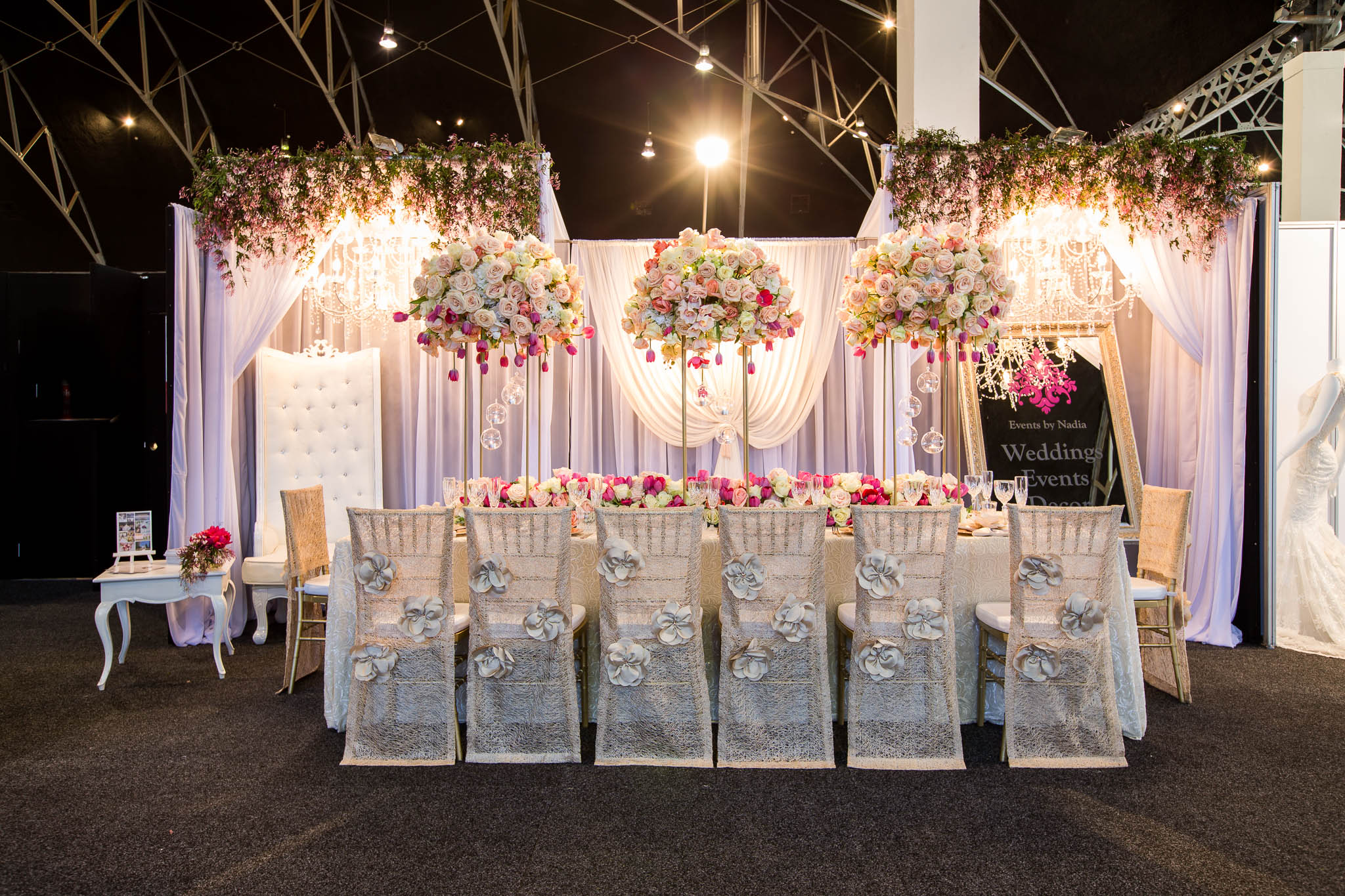Kings table centrepiece consisting of gold Carly stands with fresh florals, hanging tea lights, floral runner and PB Luxury Linen Champagne Heather chair backs, white chiffon backdrop with canopy, florals and 16 arm wrought iron chandeliers - Image 1.jpg