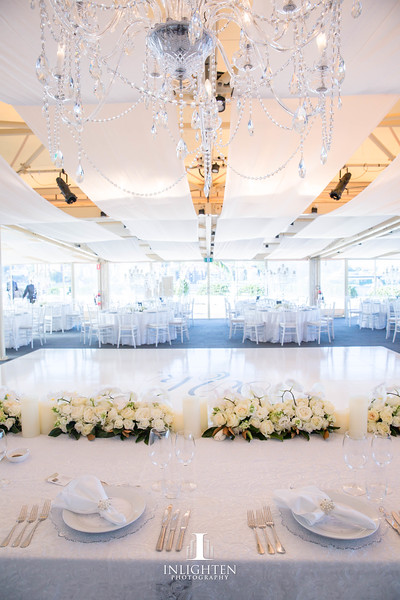 38 Kayla & Joe - Opera Point Marquee_White Windsor luxury linen_white ceiling flat sails_ bridal table_long and low_LED pillar candles_White Tiffany chairs_pearl napkin rings.jpg