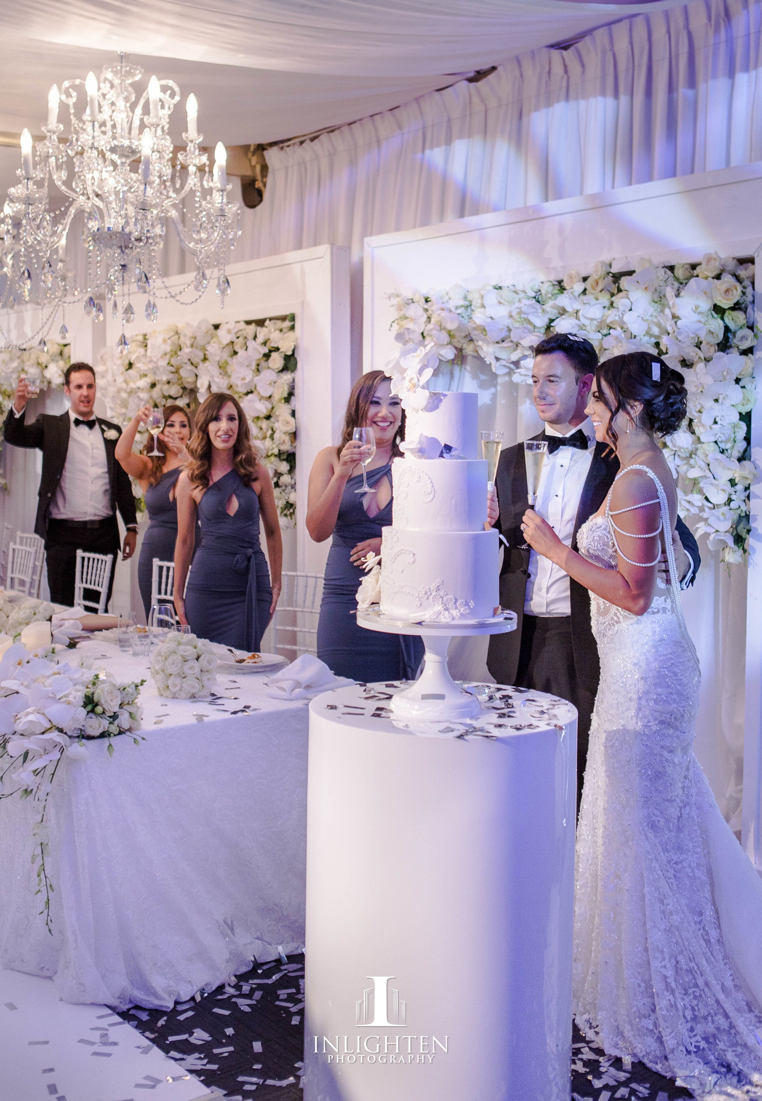 27 Kayla & Joe - Opera Point Marquee_Bridal table long low_custom built frames_fresh flowers_LED pillar candles_Sofia chandelier_white Windsor luxury linen_white round cake table_ceiling draping.jpg