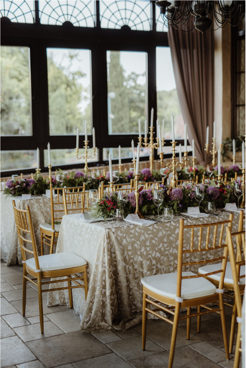 11th_century_fortress_gold_tiffany_chairs_floral_runner_greenery_purple_gold_candlesticks_LED_candles.png