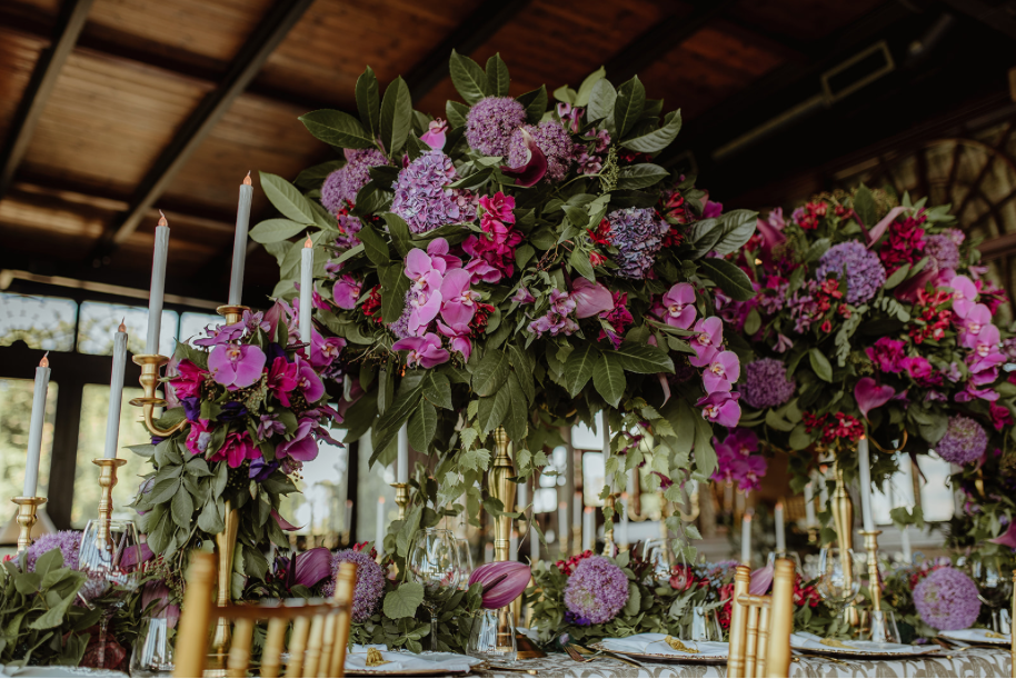 centrepiece_purple_pink_greenery_centrepiece_gold_stand_gold_tiffany_chairs_gold_candleabra_LED_candles_floral_tablerunner_11th_century_fortress.png