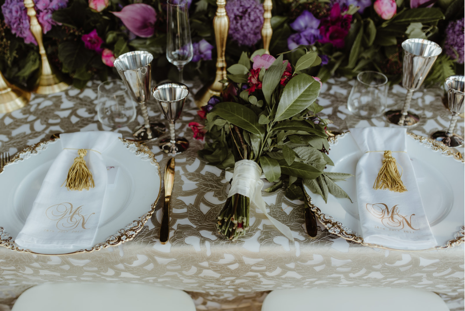 charger-plates_monogram-linen_gold_tassal_bouquet_gold_cutlery_luxury_linen_silver_wine_glases_gold_candlesticks_purple_florals.png