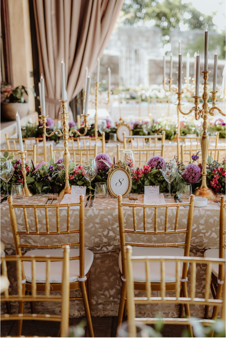 gold_tiffany_chairs_floral_runner_purple_pink_gold_candlesticks_LED_candles_gold_tablenumber_luxury_linen.png