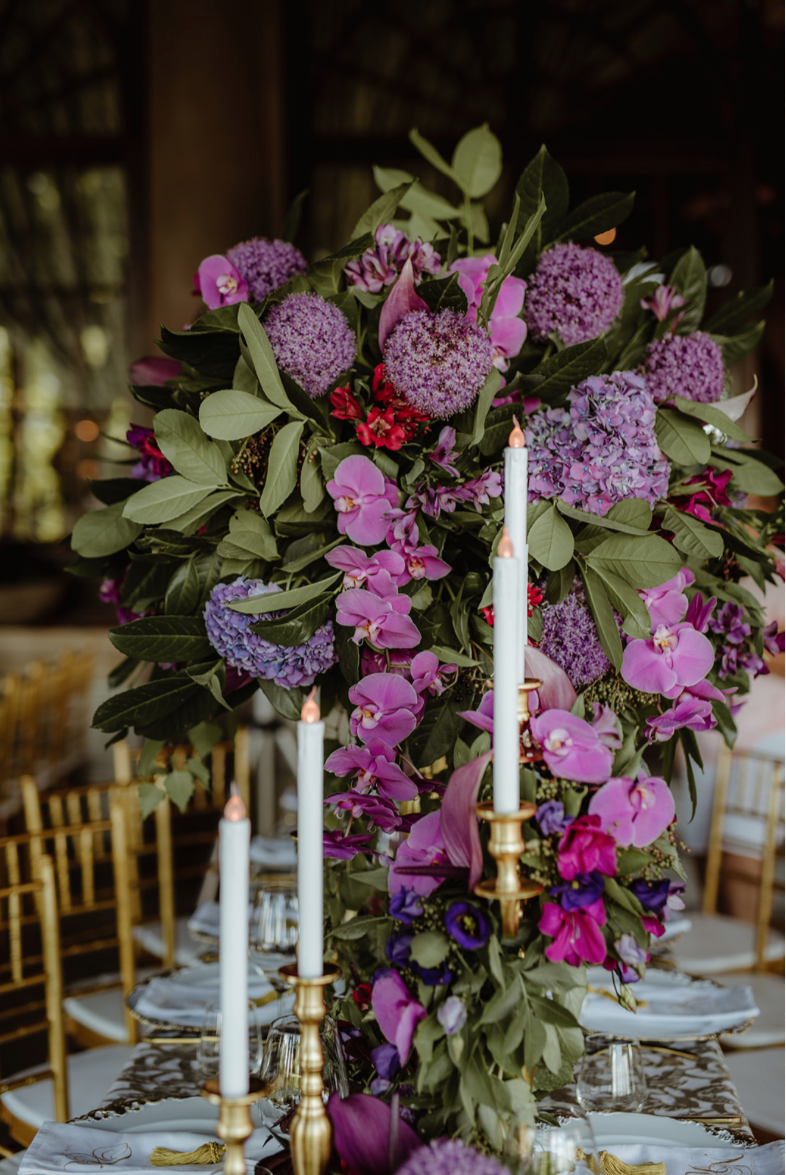 LED_candles_gold_tiffany_chairs_purple_flower_centrepiece_luxury_linen_napkin_monogram_charger_plates.png