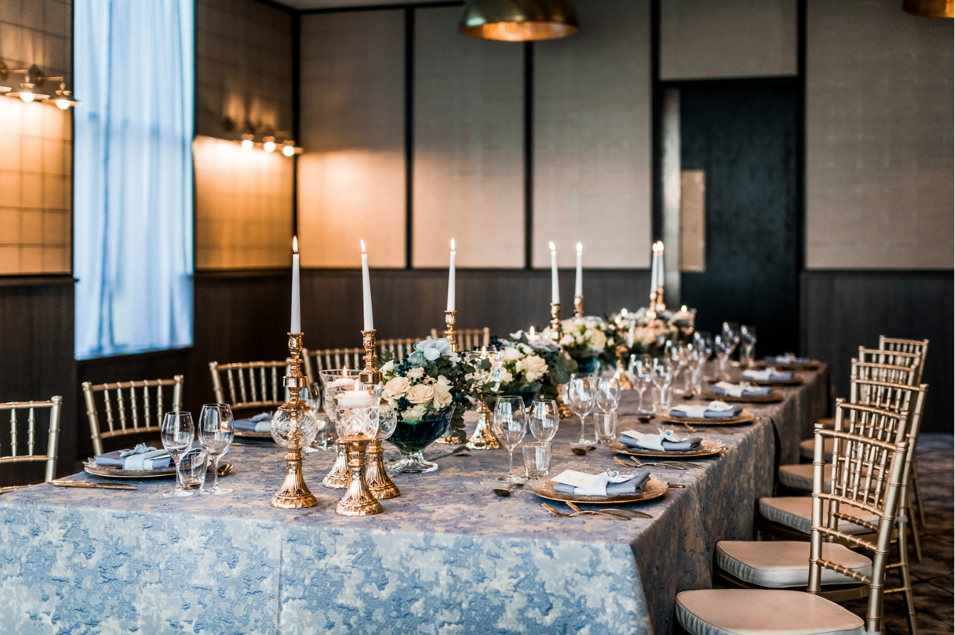 slate_plaster_luxury_linen_wedding_decor_sydney_tablecloth_blue_gold_theme_table_setting_candles_flowers_inlighten_photography.png