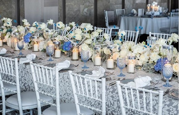 White_anita_blue_underlay_silver_charger_plate_blue_theme_white_tiffany_chair_centrepeice_white_flowers.png