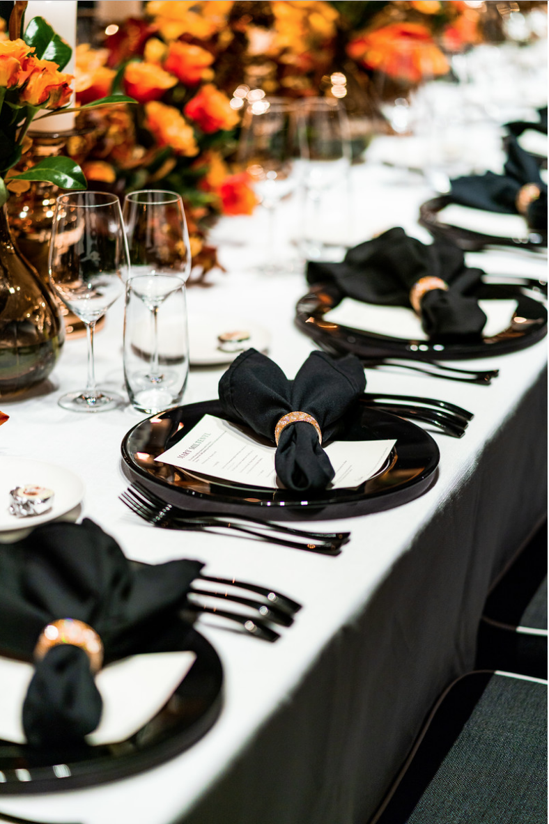 corporate_event_design_events_by_nadia_fresh_flowers_orange_inlighten_photography_black_charger_plate_cutlery_candle_stick_gold_napkin_ring_menu_cystal_glasswear.png