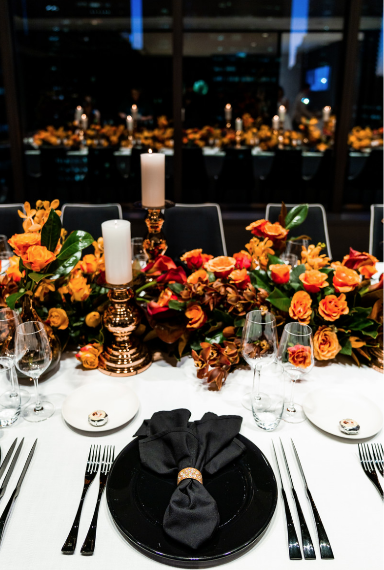 corporate_event_design_events_by_nadia_fresh_flowers_orange_inlighten_photography_black_charger_plate_cutlery.png