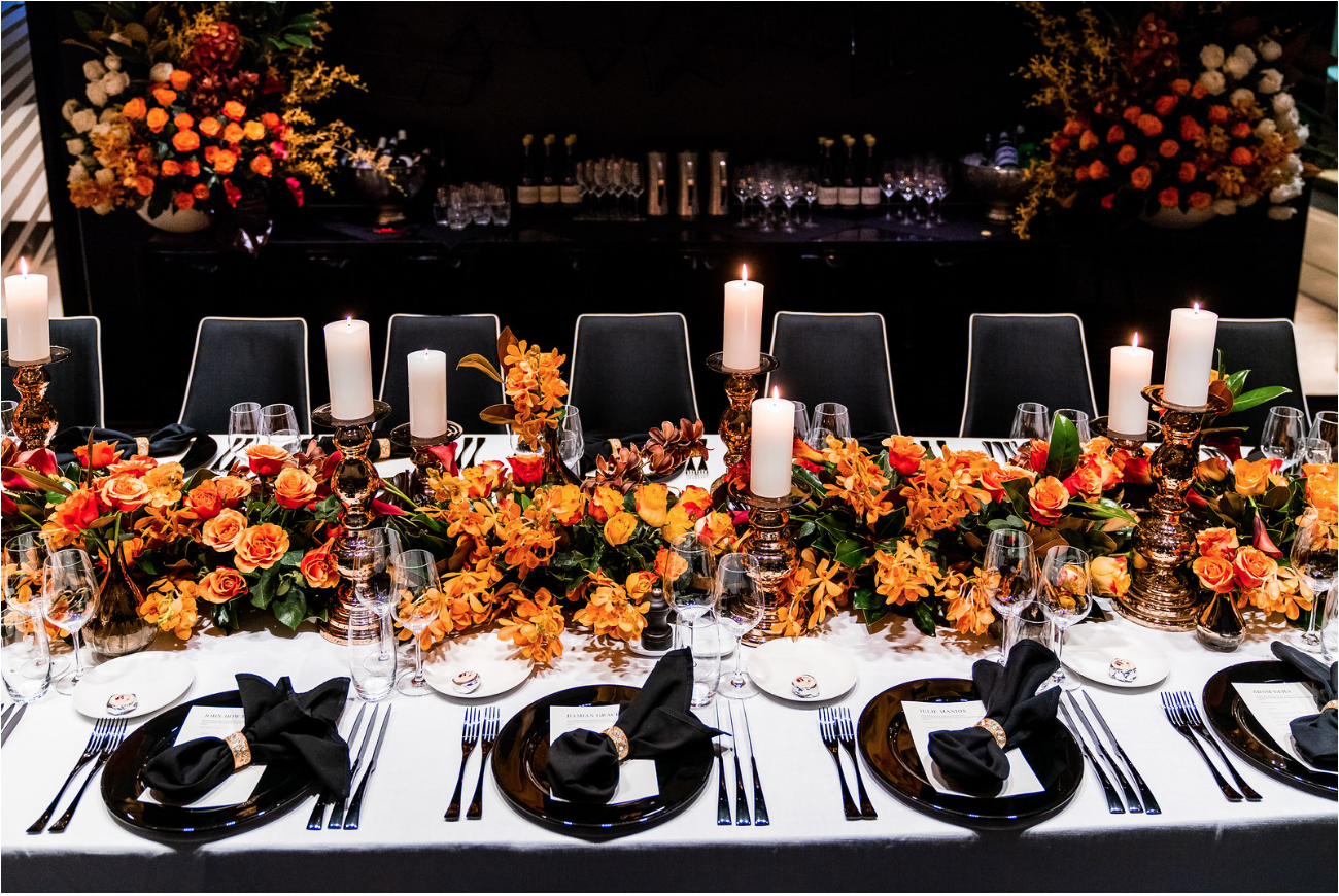 corporate_event_design_events_by_nadia_fresh_flowers_orange_inlighten_photography_black_charger_plate_cutlery_candle_stick_gold_napkin_ring_king_table_setting.png