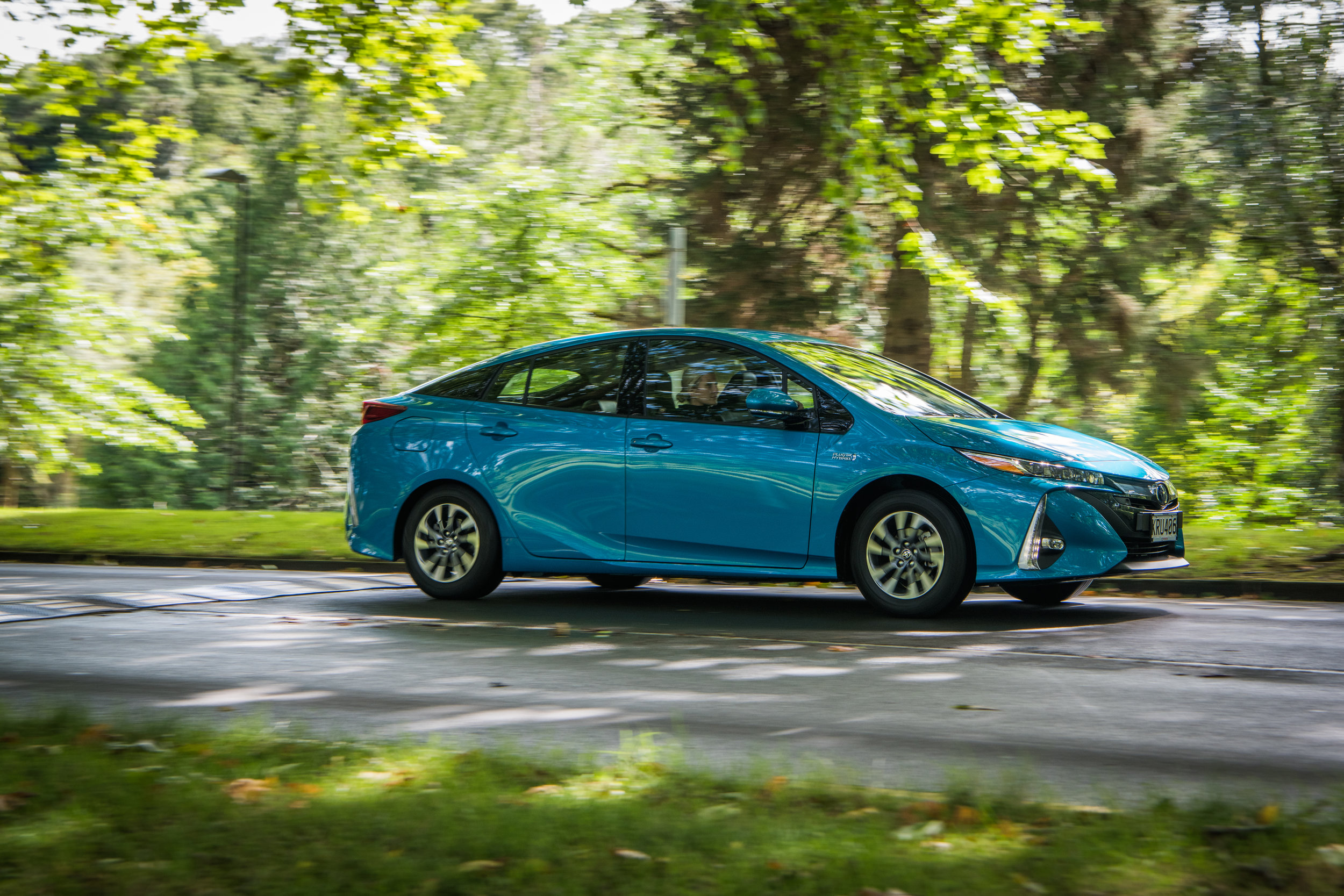 2018 Toyota Prius Prime, Blue magnetism, front three quarter moving shot.jpg