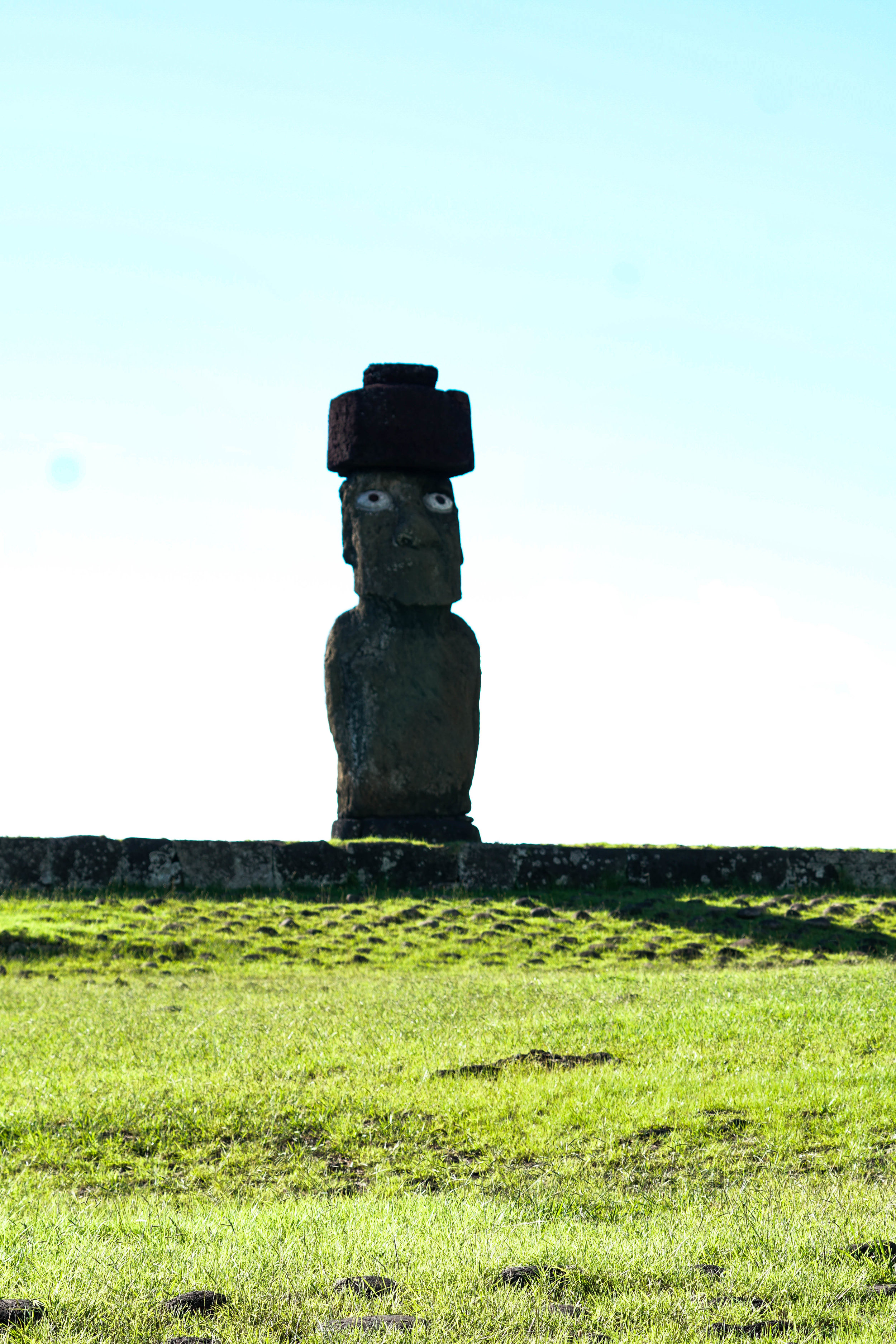 This moai is a re-creation, erected to demonstrate what a complete moai would have looked like, complete with red top hat and gemstone eyes.