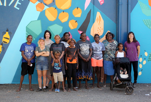 Hidden Valley Artists, Province's Al Dadak, WTS Coordinator Alex Hullah and Tangentyere Artist Manager Jo Byrne pose in front of the Ewyenper Atwatye Mural, 2015