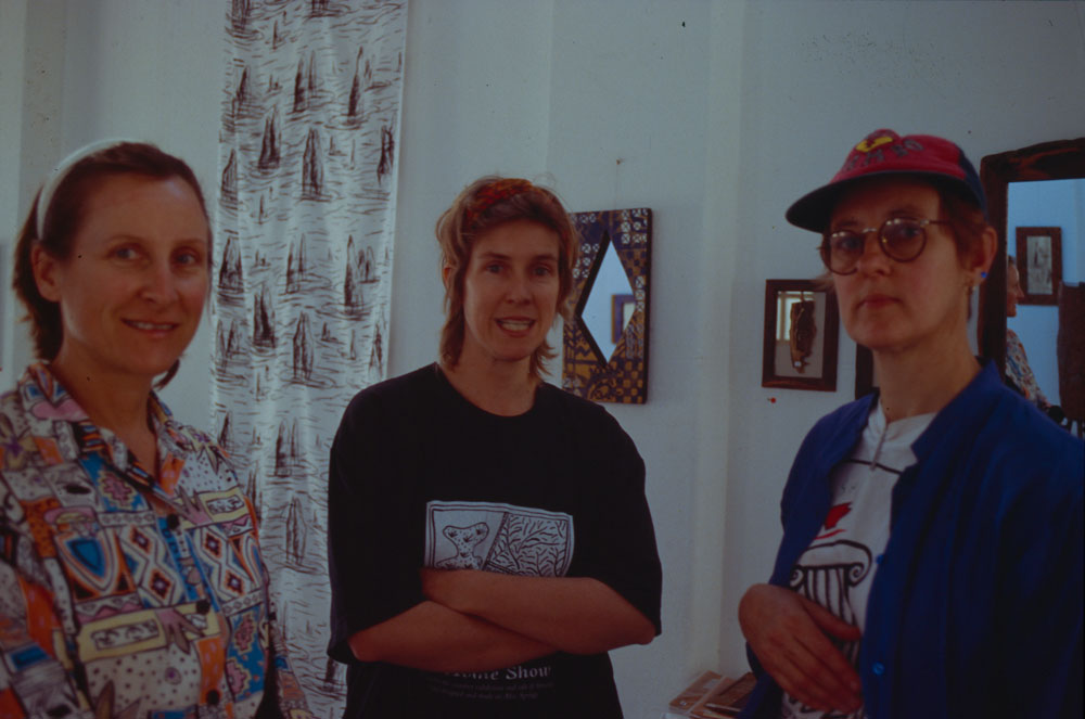 2/5 of the Founding Members: (L) Angela Gee & (R) Pip McManus, (M) Mary-Lou Nugent, with founding member Jan Mackay's hanging fabric artwork in the background. Circa 1995.