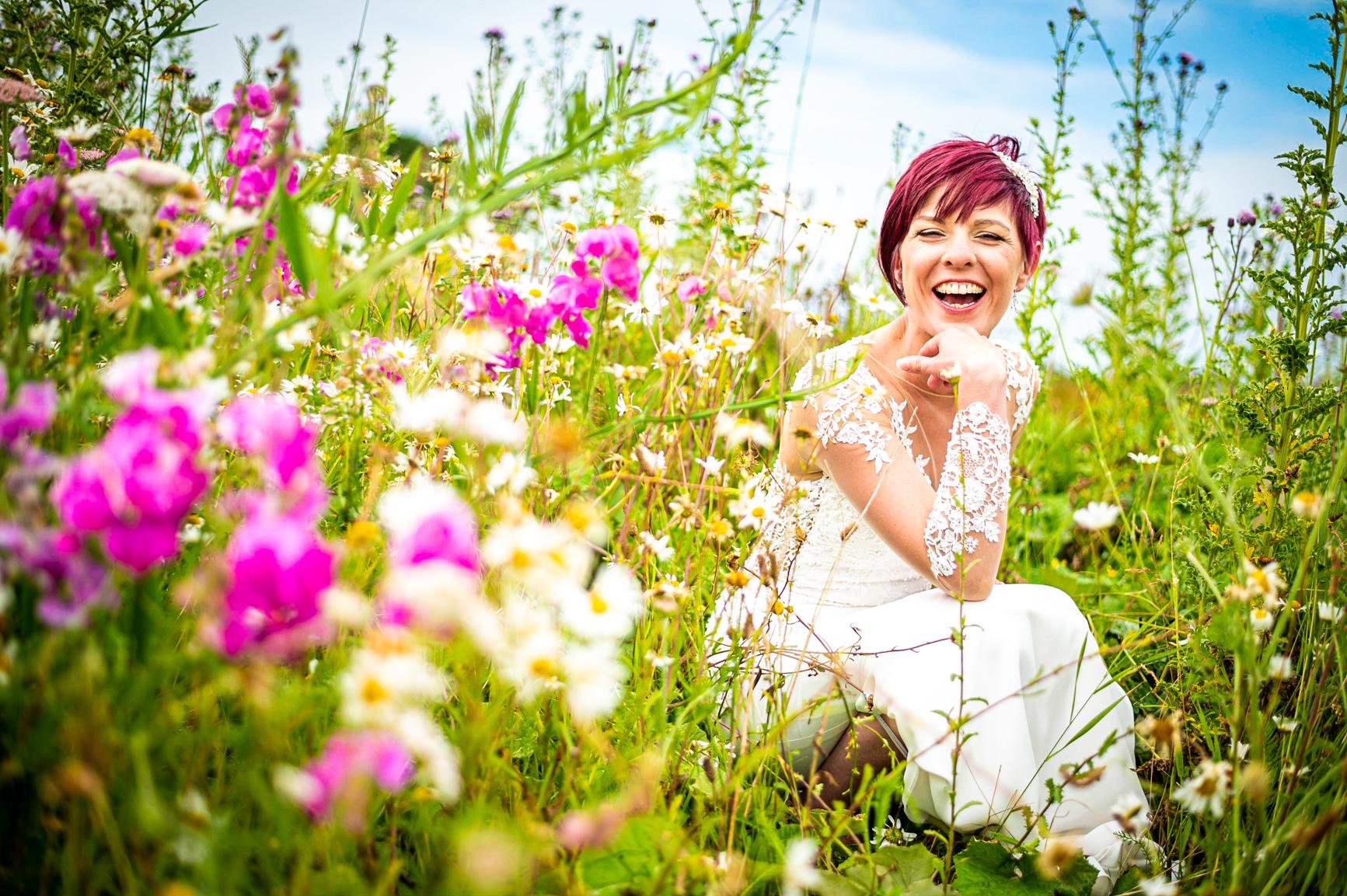 Bride laughing in wildflowers