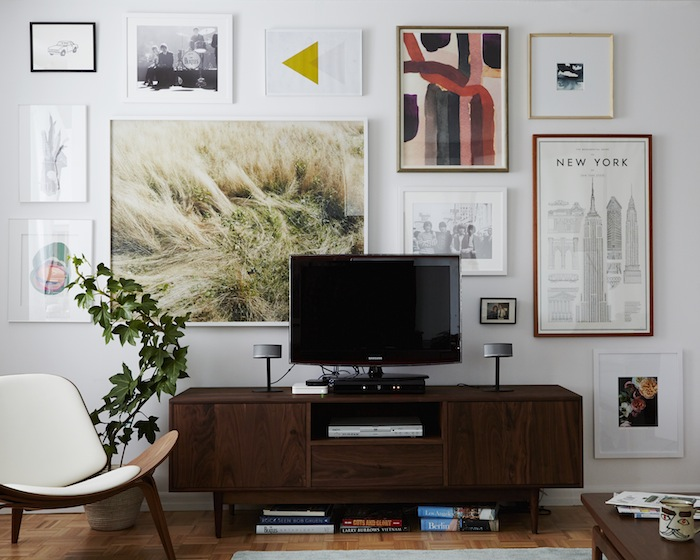 THIS GALLERY WALL IS HELPING TO TAKE FOCUS OFF OF THE TV.  (VIA EMILY HENDERSON )