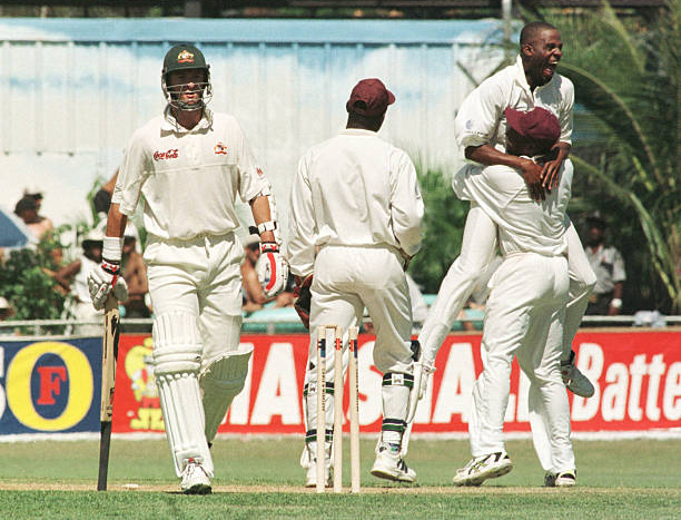 Nehemiah Perry is embraced by Brian Lara after bowling Mark Waugh for 67 in 1999.