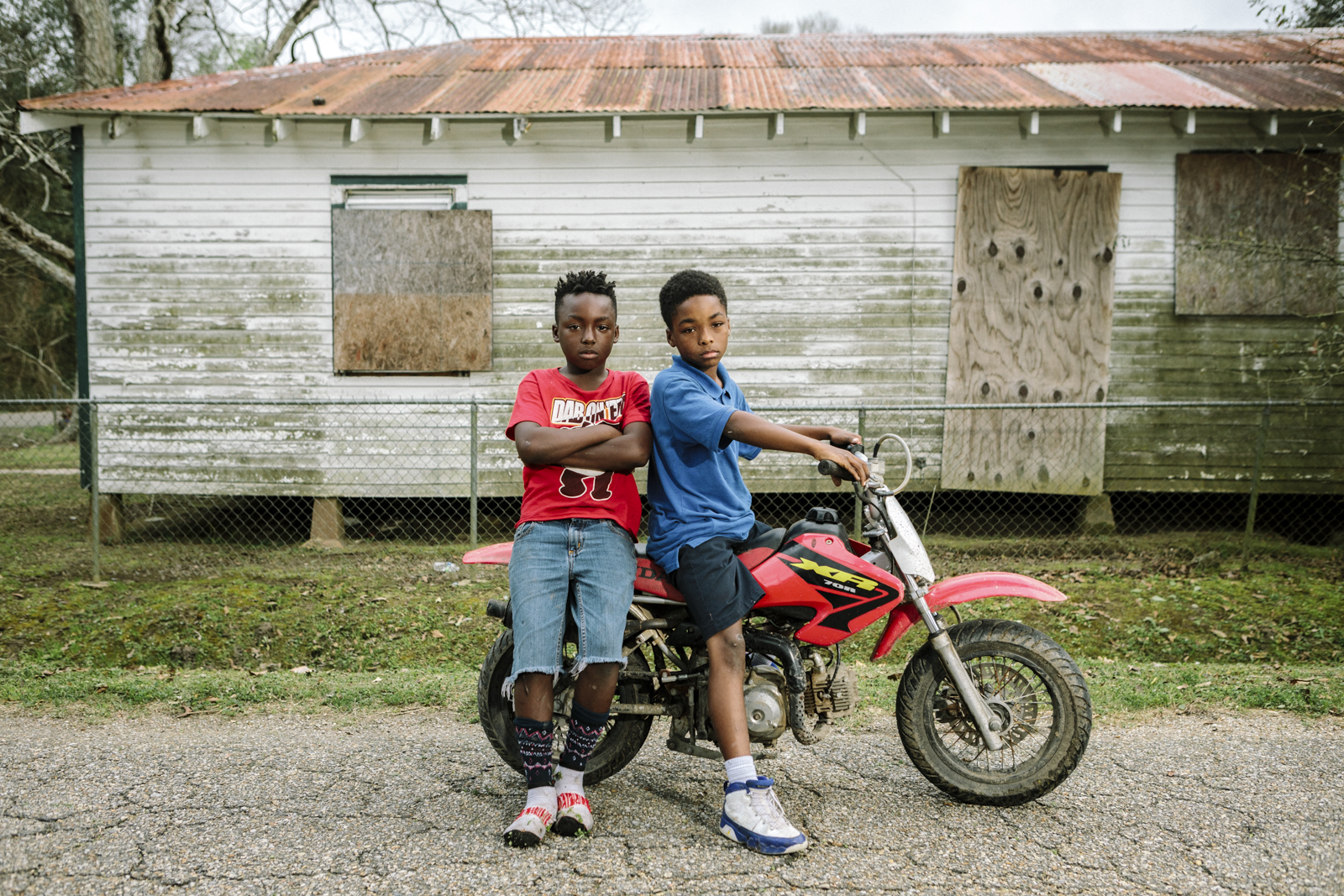 Reserve, LA - Feb 20, 2017 - Local residents Jaden James (9, L) and Lance Bovie (9) pause on Robinet Drive, less than a block from the fence line of the Dupont/Denka plant. Many of the homes in the area have been vacated as residents have either died or left town.