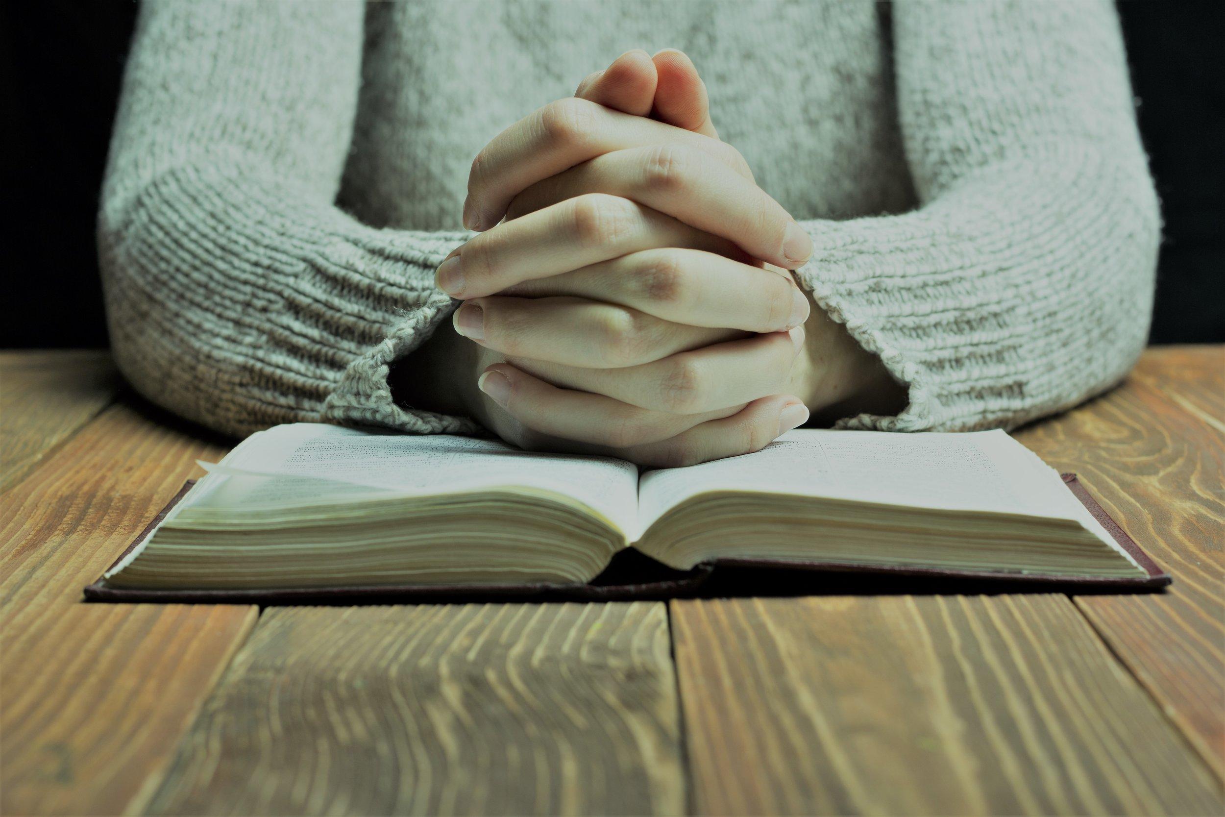 Folded hand on Bible Neo.jpeg