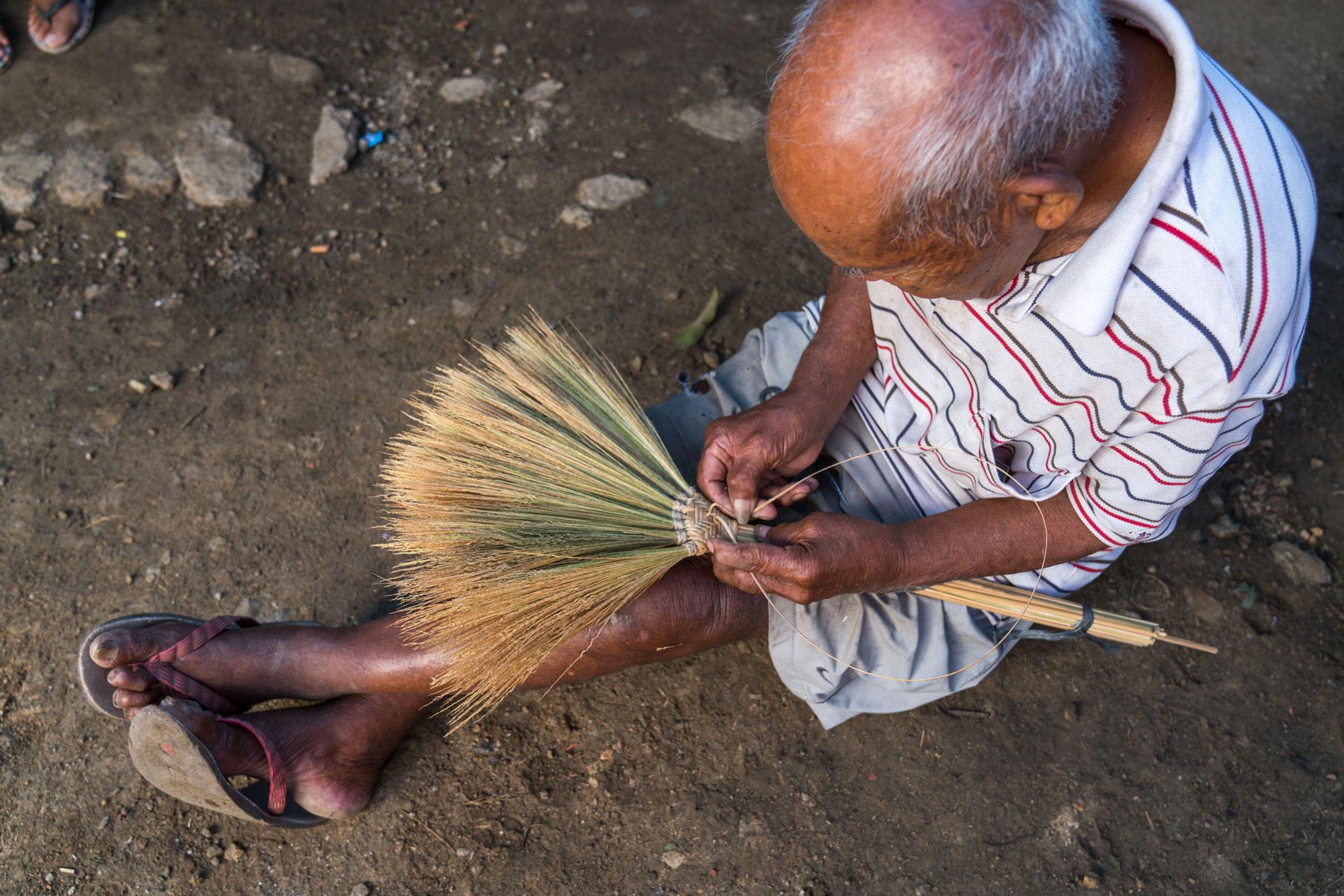 a man weaves a wicker broom
