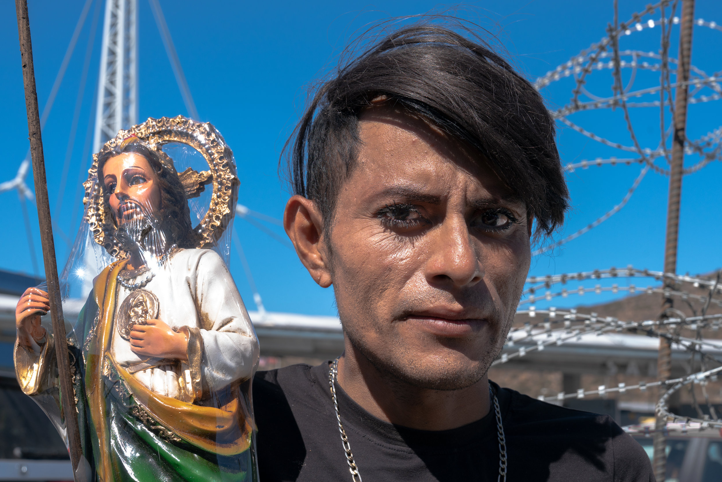 A man hawks a religious statue to the people in cars waiting in line to cross the American border.