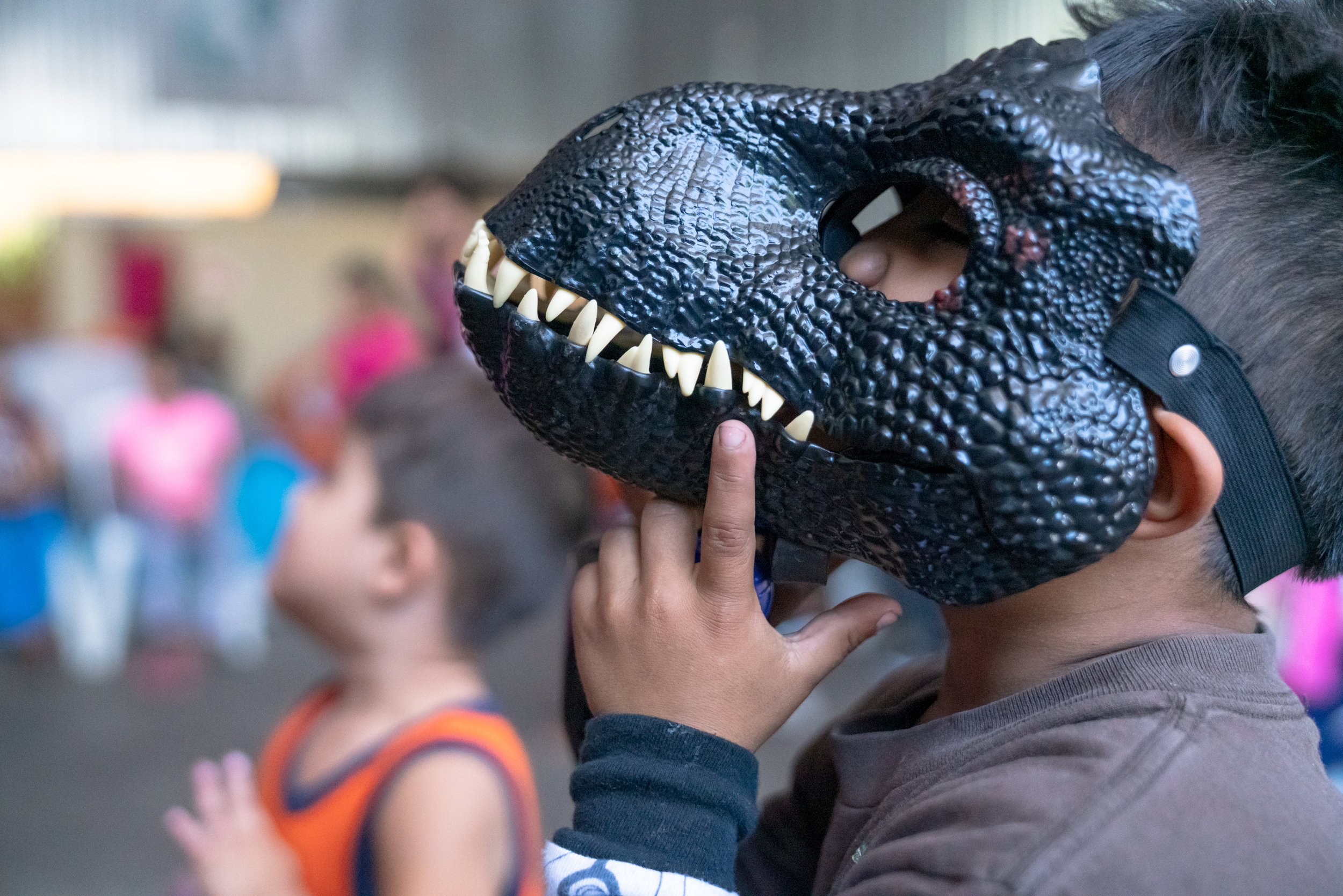A young boy wears his dinosaur mask in a refugee shelter.