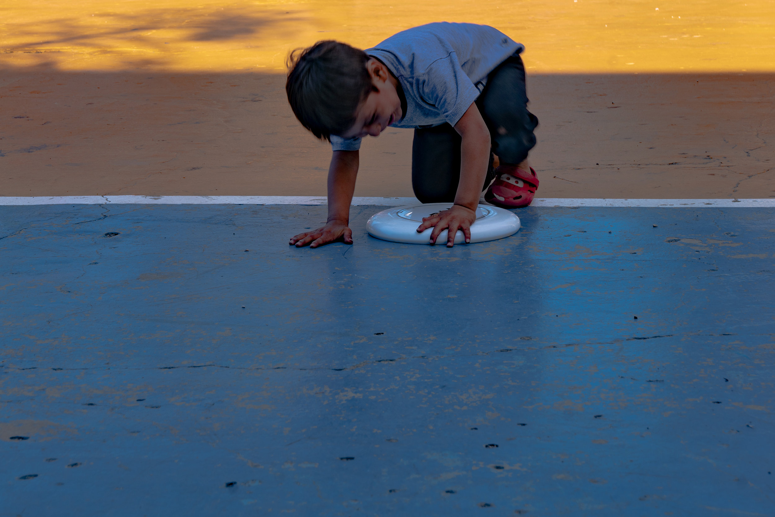 A young boy plays with a Frisbee at a park by the refugee shelter that we visited.