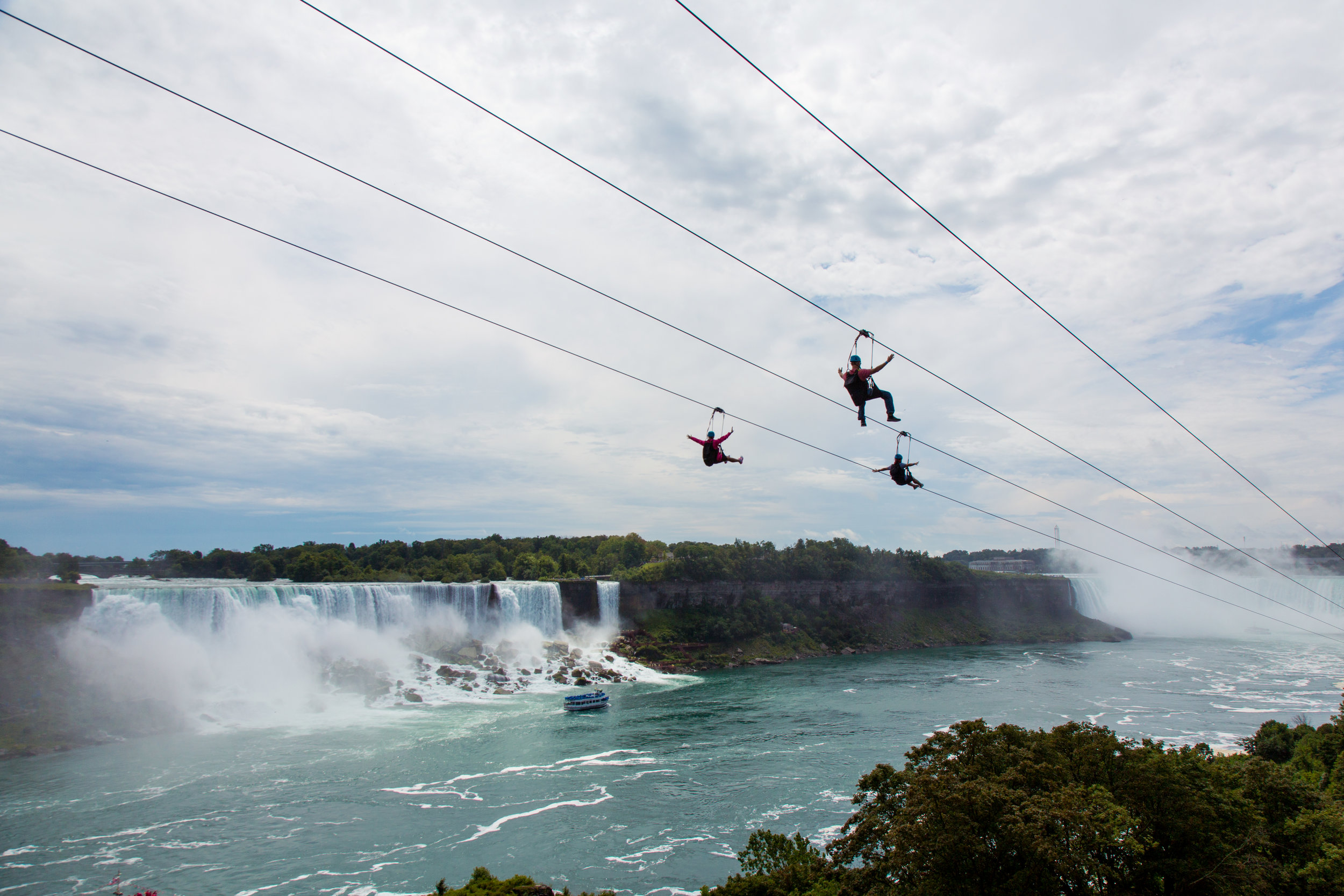 Zip liners take a ride on the Canadian side, with the American falls, and the Maid of the Mist in the background.