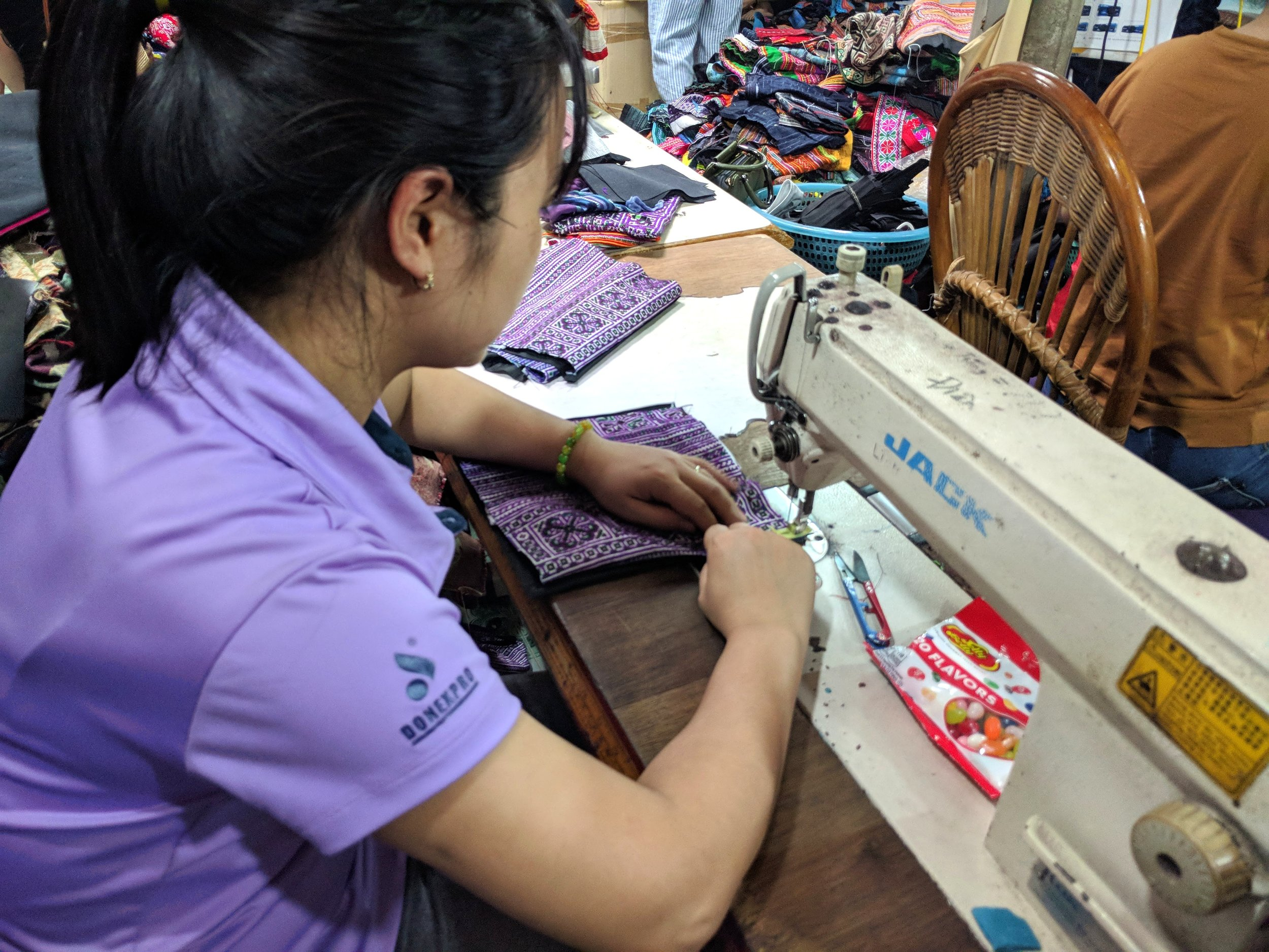 Hien's employee, Lien, sews a zippered pouch. This job has provided her with steady work for over 8 years.