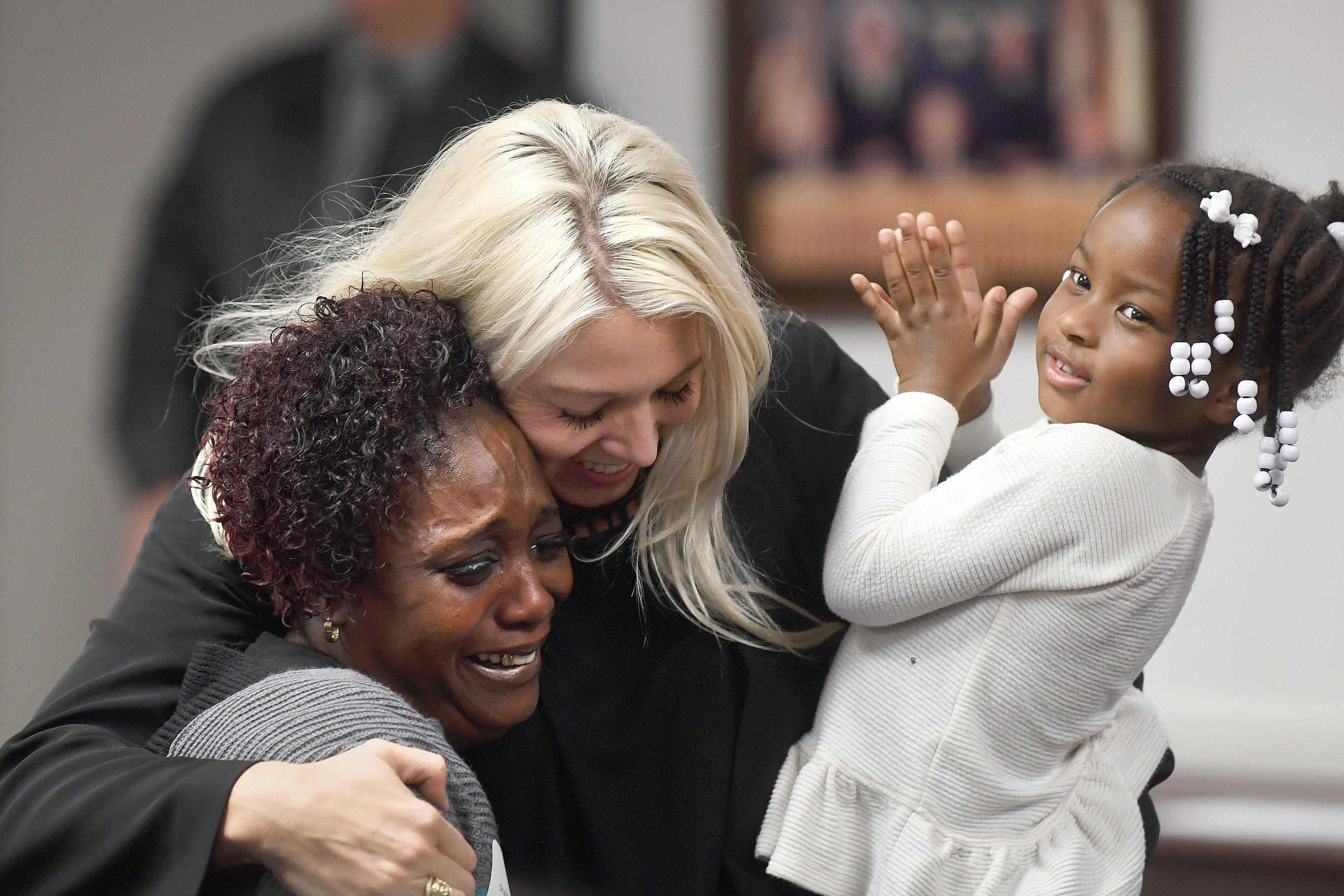 Shalonda Robinson, left, cries tears of joy while being hugged by attorney Amanda Buenger during Brazos Valley Adoption Day on Wednesday, Nov. 14, 2018, in Bryan, Texas. Buenger is holding Robinson's three-year-old granddaughter, Ju'Torrah, one of four children Robinson adopted during Brazos Valley Adoption Day. (Laura McKenzie/The Eagle)