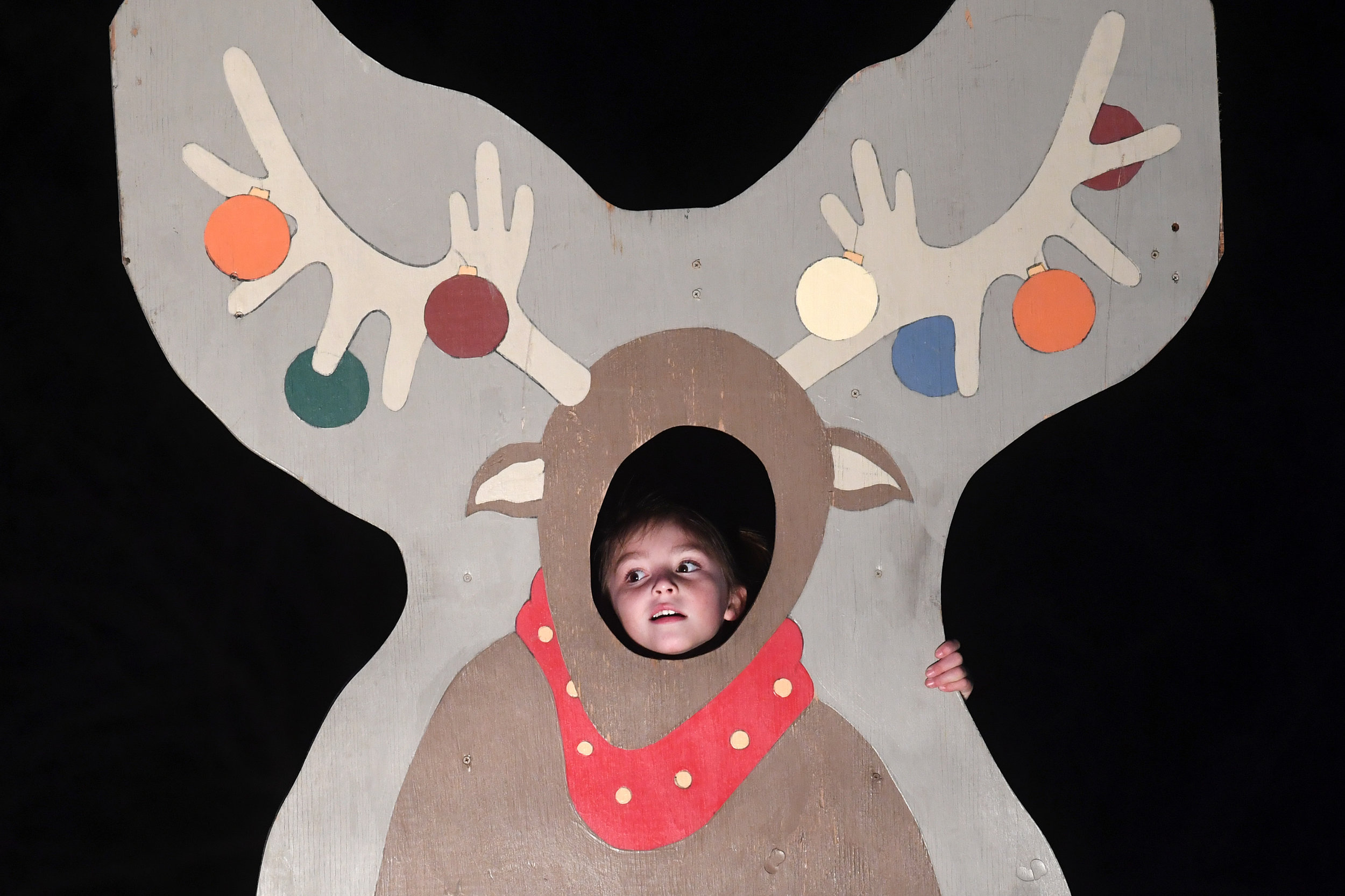A child looks through a reindeer cutout at Stephen C. Beachy Central Park during the City of College Station's Christmas in the Park on Friday, Nov. 30, 2018. Admission to the event was free and activities included hayrides, live entertainment, a petting zoo, inflatables, snow slides and photos with Santa. (Laura McKenzie/The Eagle)