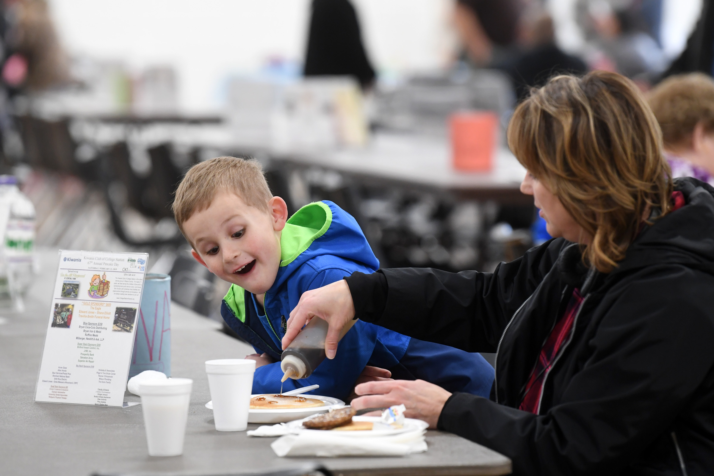 Evan Eneks, 5, smiles as his mom, Brandie, draws a happy face in syrup on his pancakes during the 67th Annual Pancake Day sponsored by the Kiwanis Club of College Station on Saturday, Feb.23, 2019, at the Brazos Center in Bryan, Texas. The event also included area non-profits offering games and crafts for children. A portion of the proceeds from Pancake Day benefitted the Fun For All Playground. (Laura McKenzie/The Eagle)