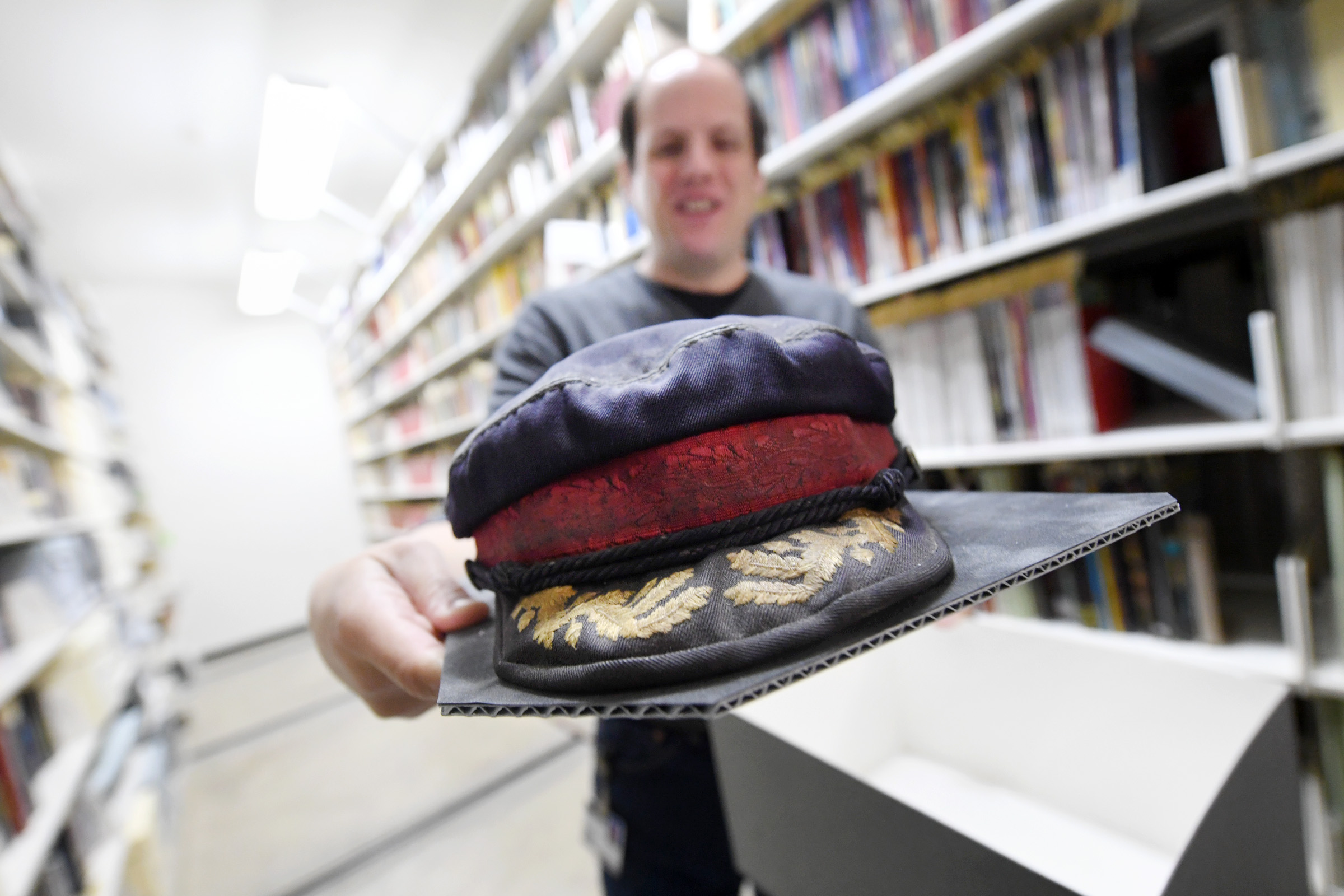 Science Fiction and Fantasy Curator Jeremy Brett holds one of author George R.R. Martin's signature fisherman caps, which is part of the collection at Texas A&M University's Cushing Memorial Library and Archives in College Station, Texas. (Laura McKenzie/The Eagle)