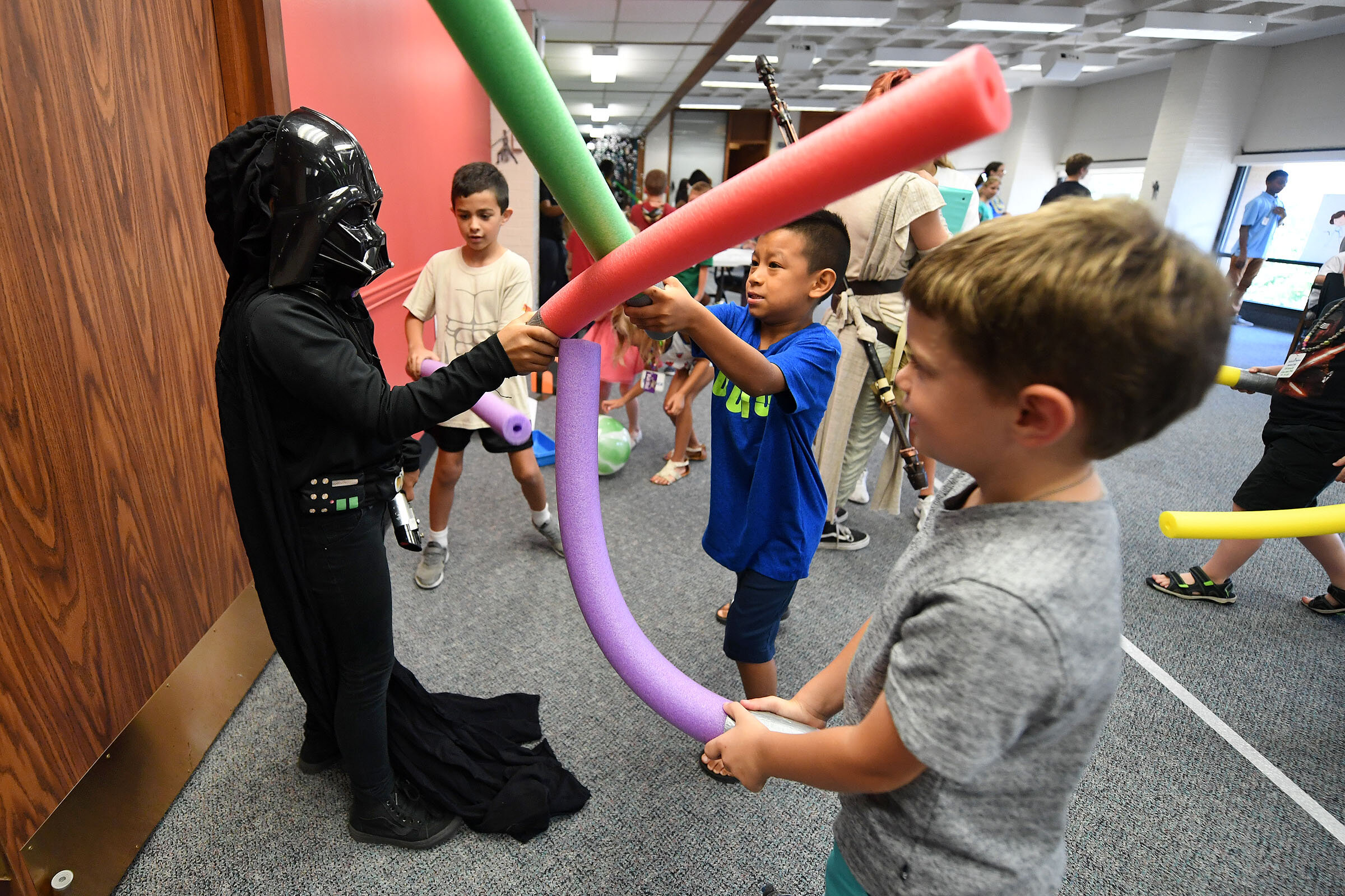 "While dressed as Darth Vader, Lexi Chapa, 9, left, playfully fights other children with foam noodle ""lightsabers"" during the Star Wars Fun event at Clara B. Mounce Public Library on Wednesday, July 10, 2019, in Bryan, Texas. The free event was part of the library's summer reading program. Other activities included ""Pin the Hair Bun on Leia"", Jedi training with balloons and a Yoda craft. (Laura McKenzie/The Eagle)"