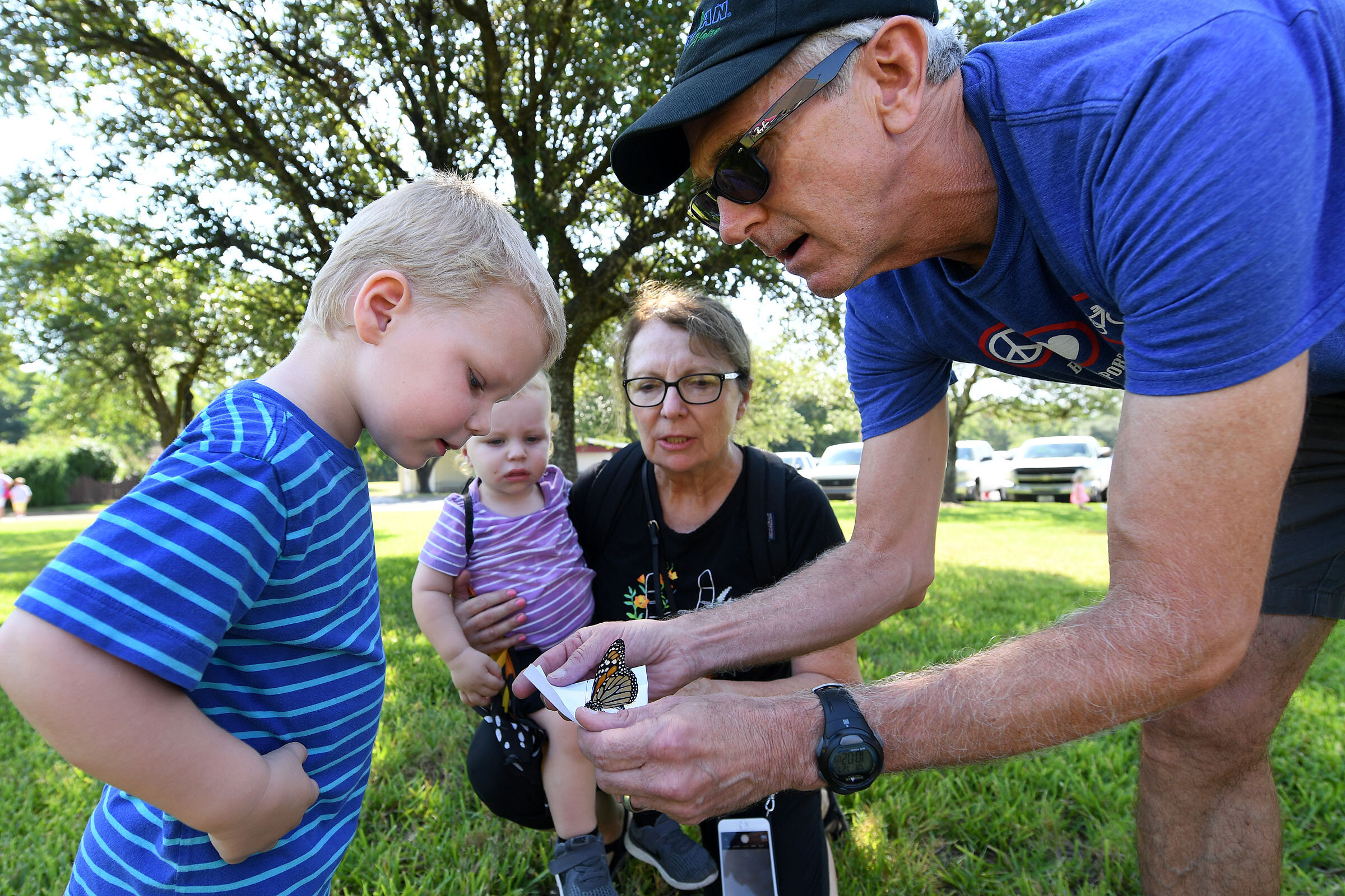 Ruthie Gray and Gary Kunkel release a monarch butterfly with their grandsons, Otis Gray, 2, left, and Walter Gray, 16 months, during the Brazos Valley Museum of Natural History's 7th annual Wish Upon a Butterfly event on Saturday, July 27, 2019, in Bryan, Texas. (Laura McKenzie/The Eagle)