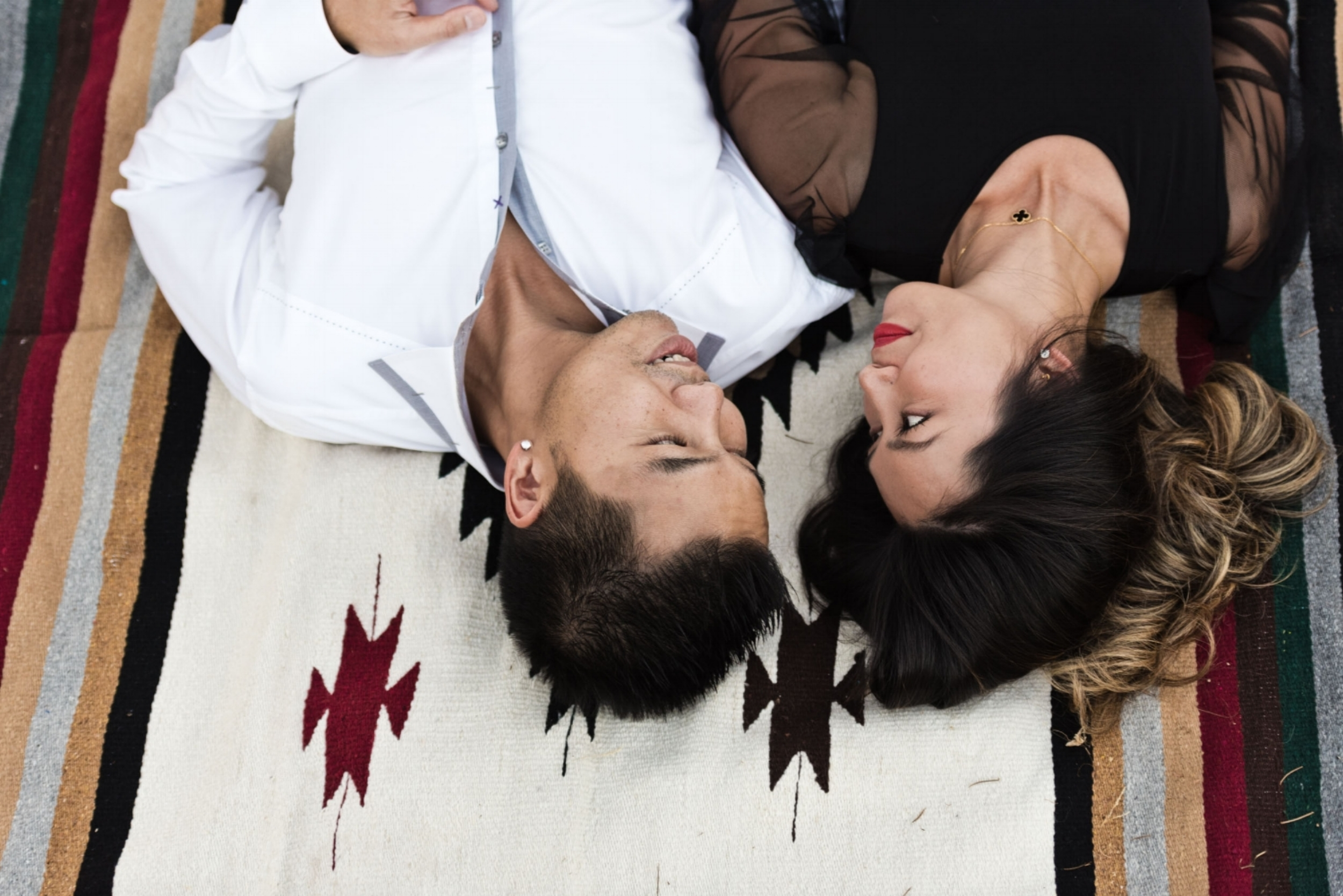 Asian couple lying in the park. Mom and dad lying on a Native American motif blanket in Cedar Grove Park in Tustin, California.