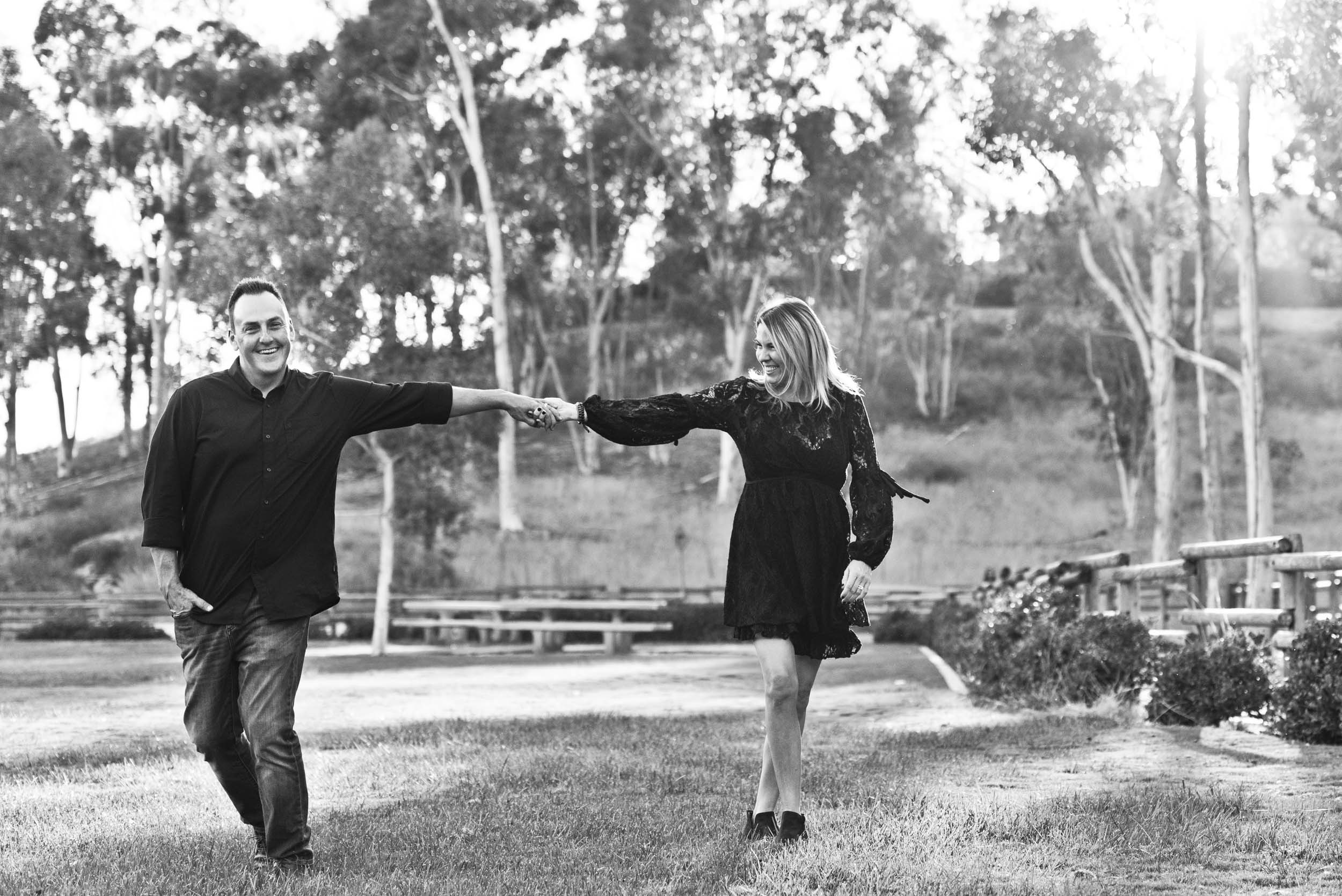 Mom and dad holding hands dancing in the park.Cedar Grove Park, Tustin, California.