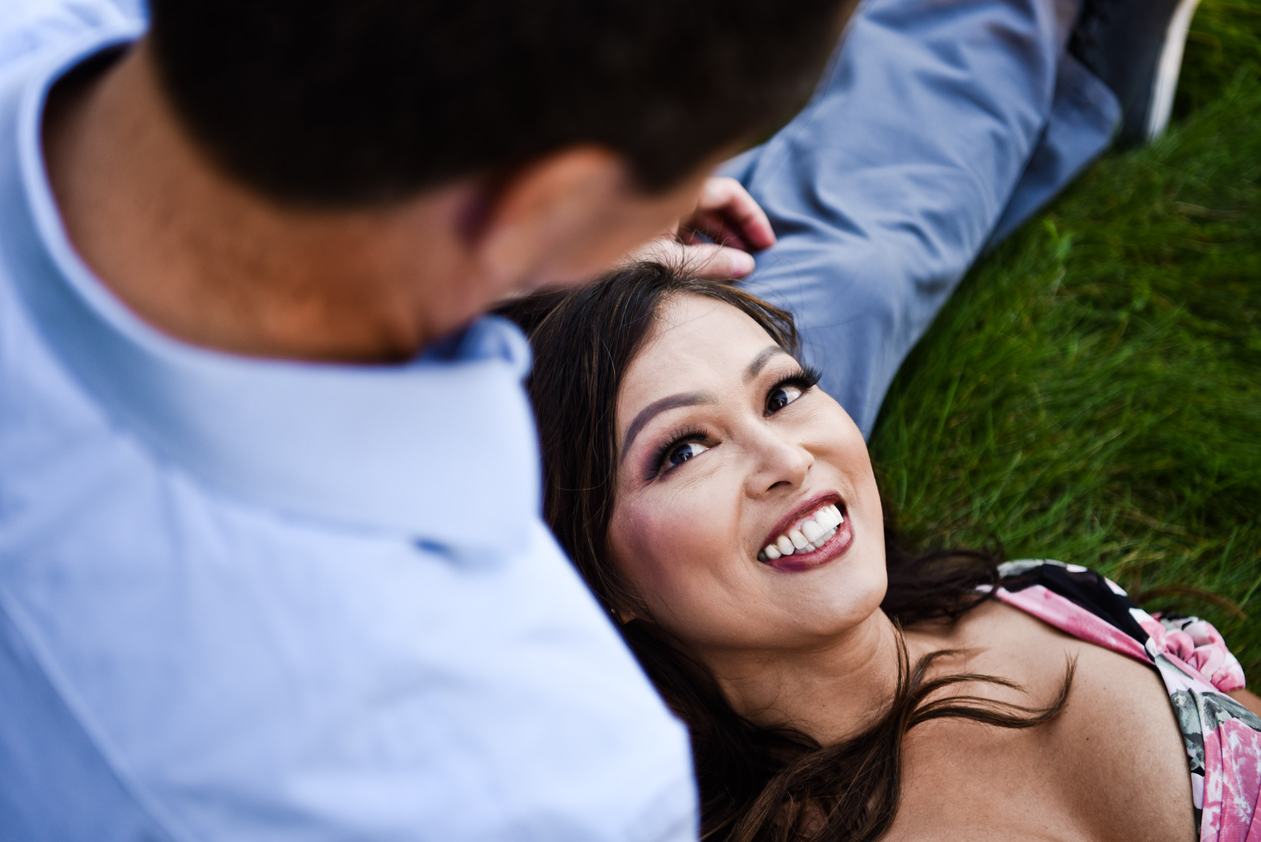 Woman gazing at husband lying on the grass in the park. Noguchi Sculptural Garden in Costa Mesa, California.