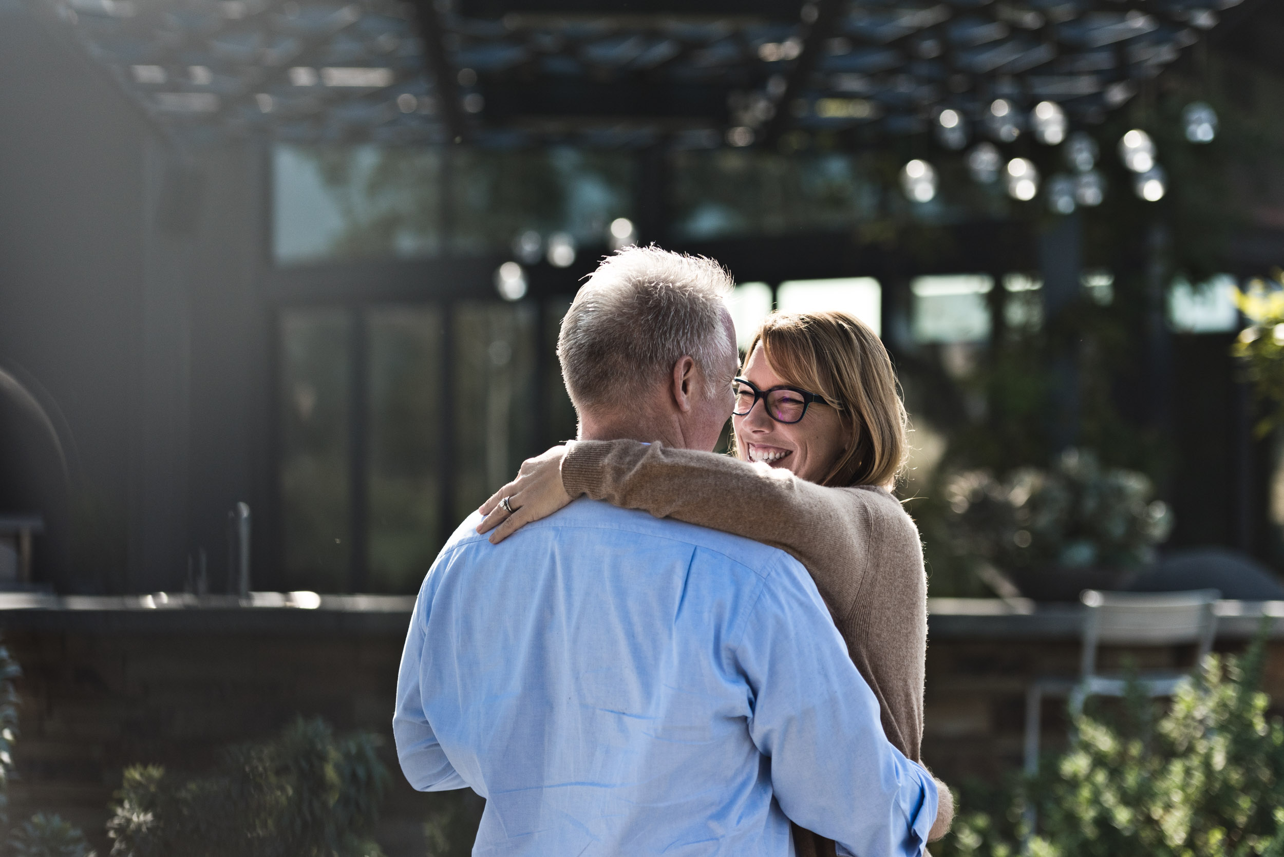 Wife smiling as husband while dancing. Beacon Park in Irvine, California.
