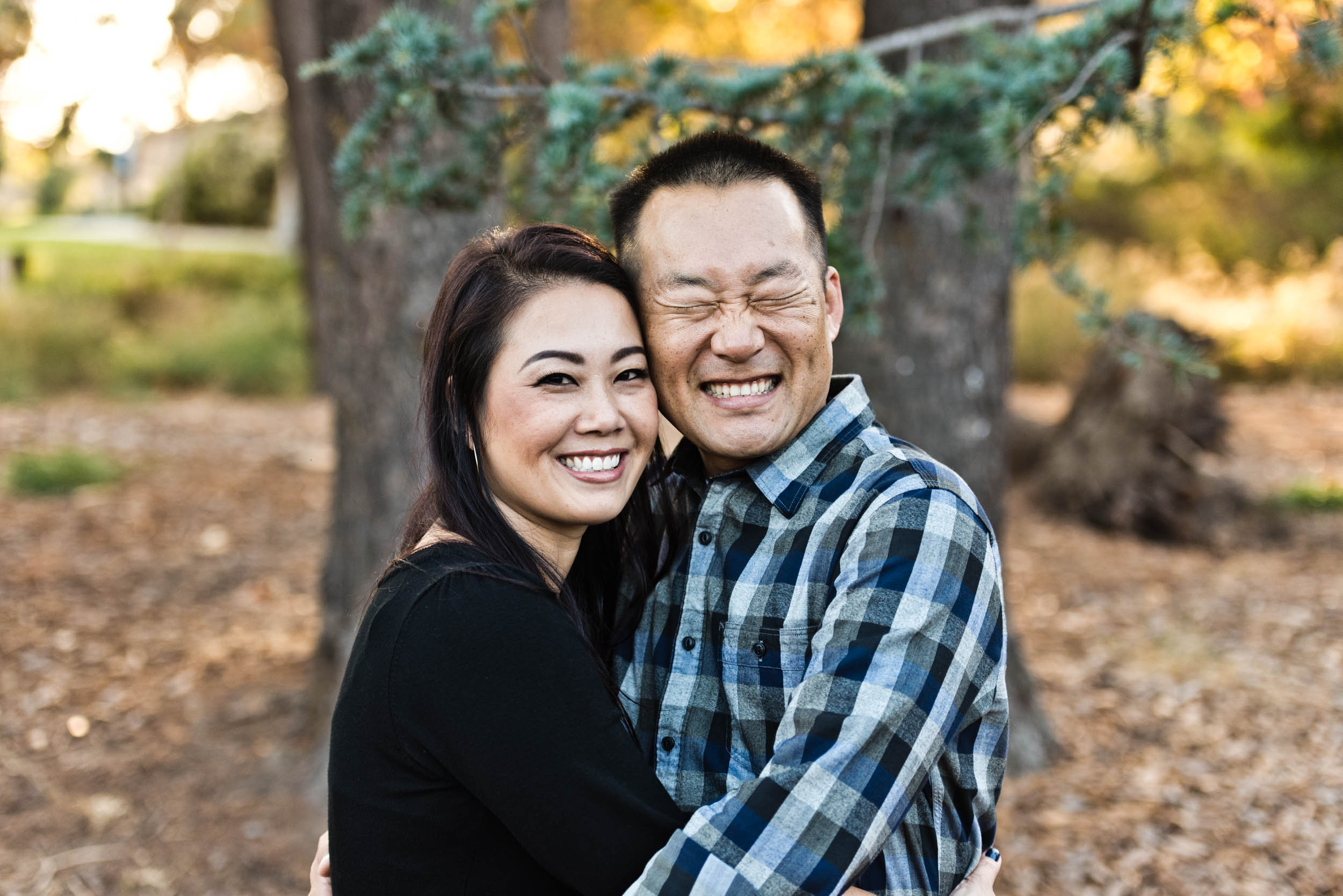 Mom and dad hugging and smiling while basking in the golden hours of the afternoon at the park. Cedar Grove Park in Tustin, California.