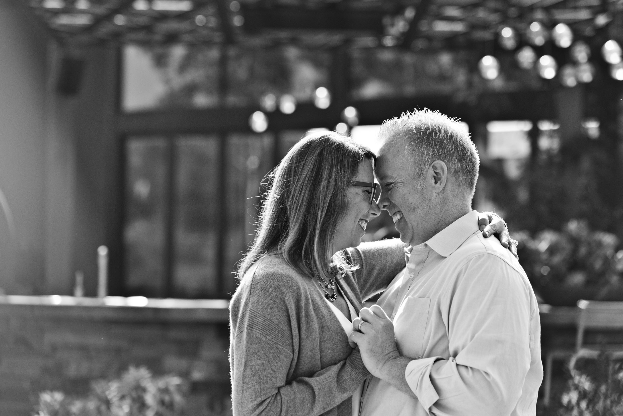 Mom and dad dancing in the park and smiling at each other.
