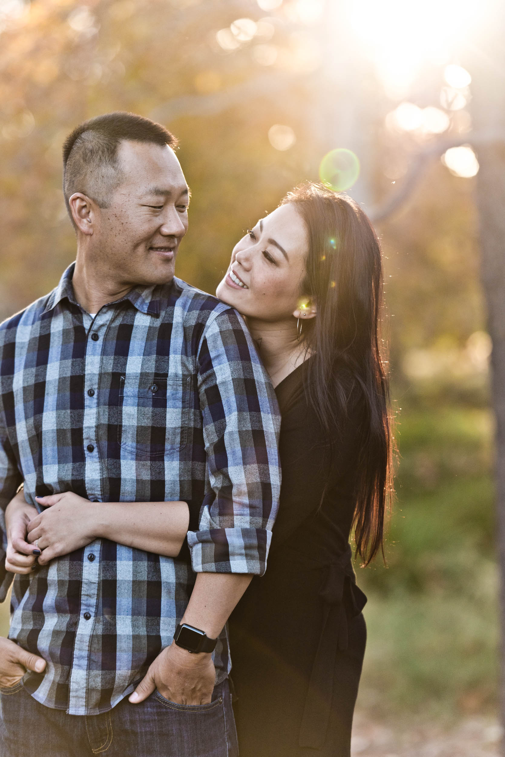 Asian couple. Mom holding dad and looking into each other's eyes in the park.