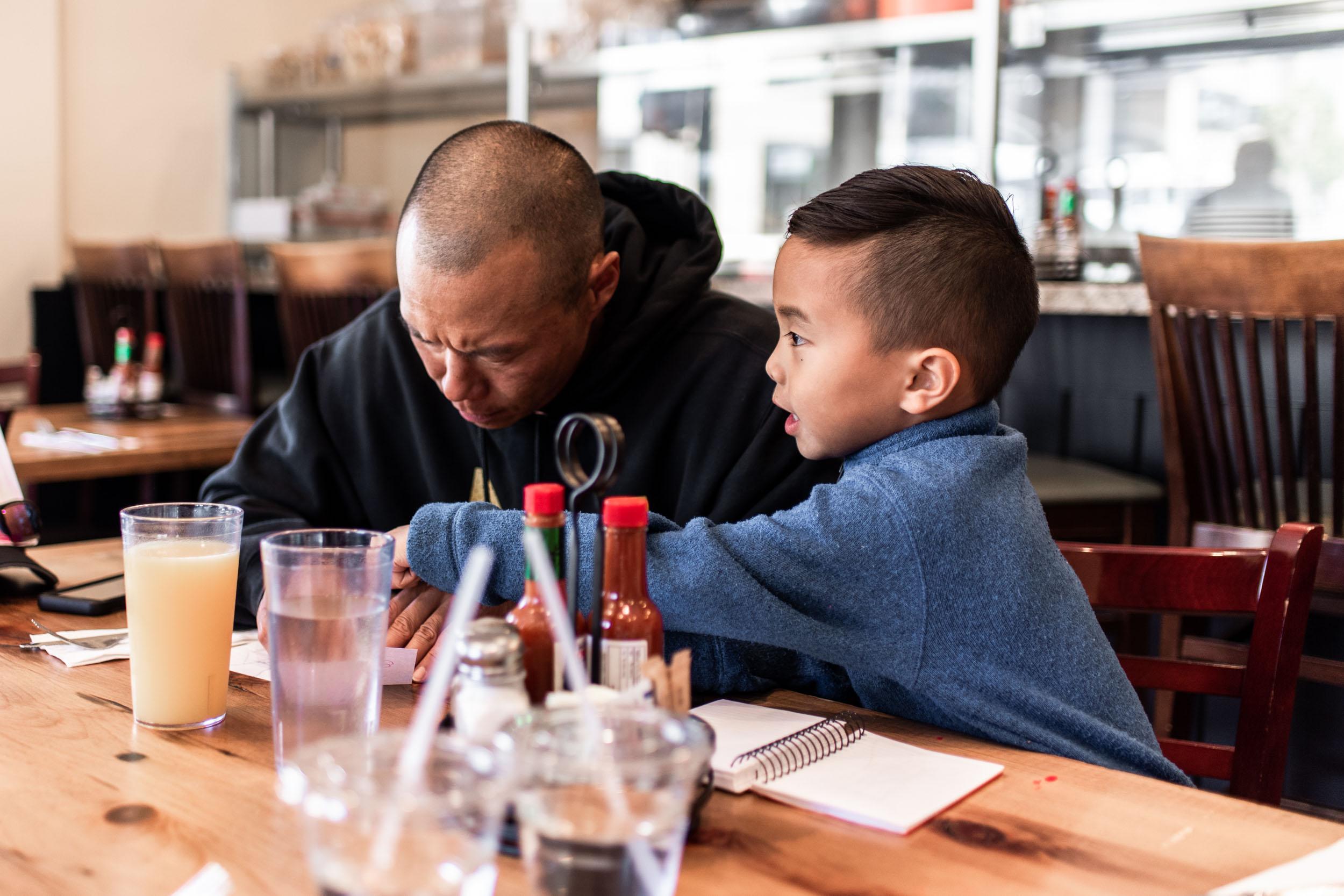 Man and kid drawing while eating breakfast at Ella's San Francisco. Lisa Hu Chen tutorial on IGTV videos.