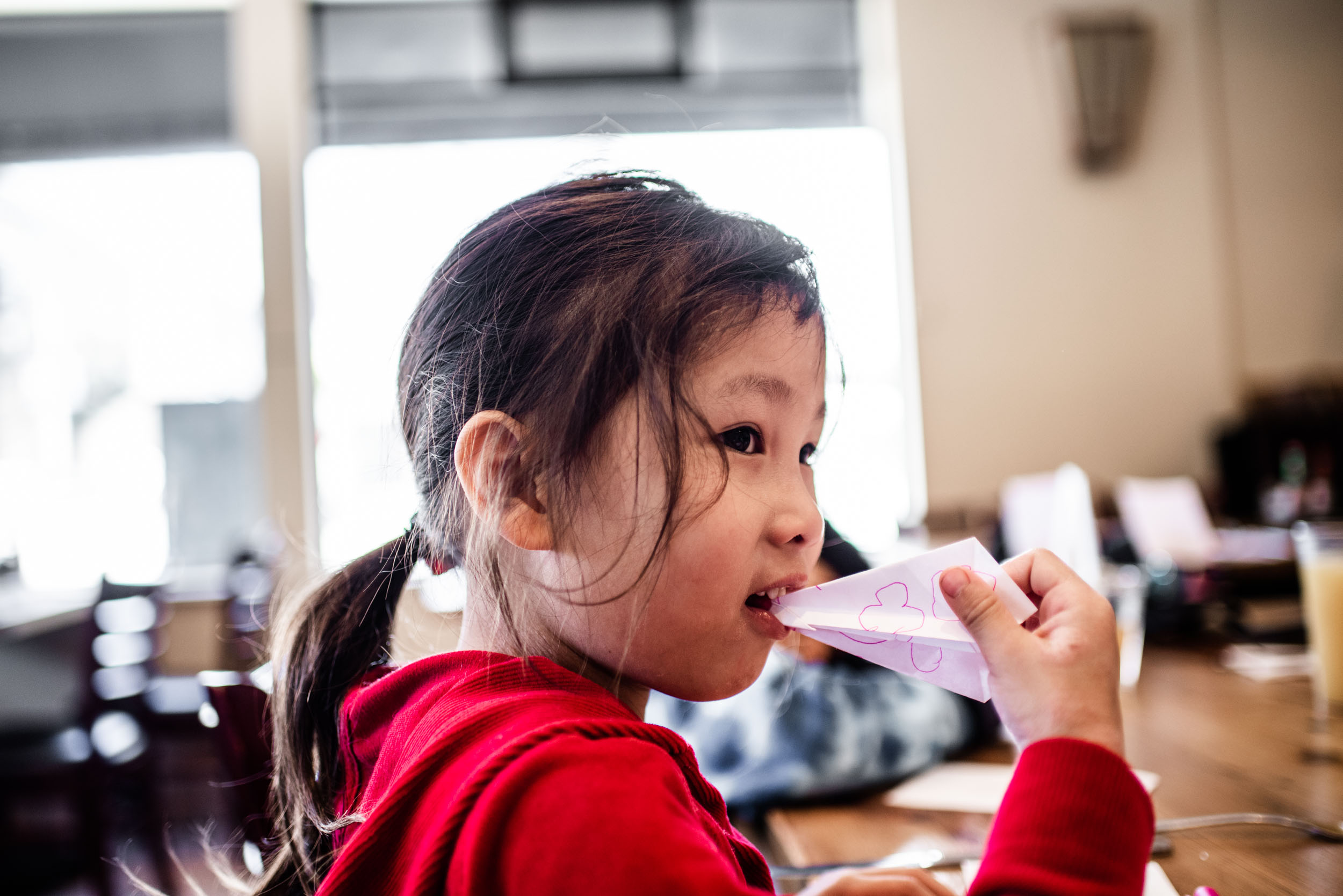 Little girl smiling with a paper airplane in her mouth while waiting for breakfast at Ella's San Francisco. Lisa Hu Chen tutorial on IGTV videos.