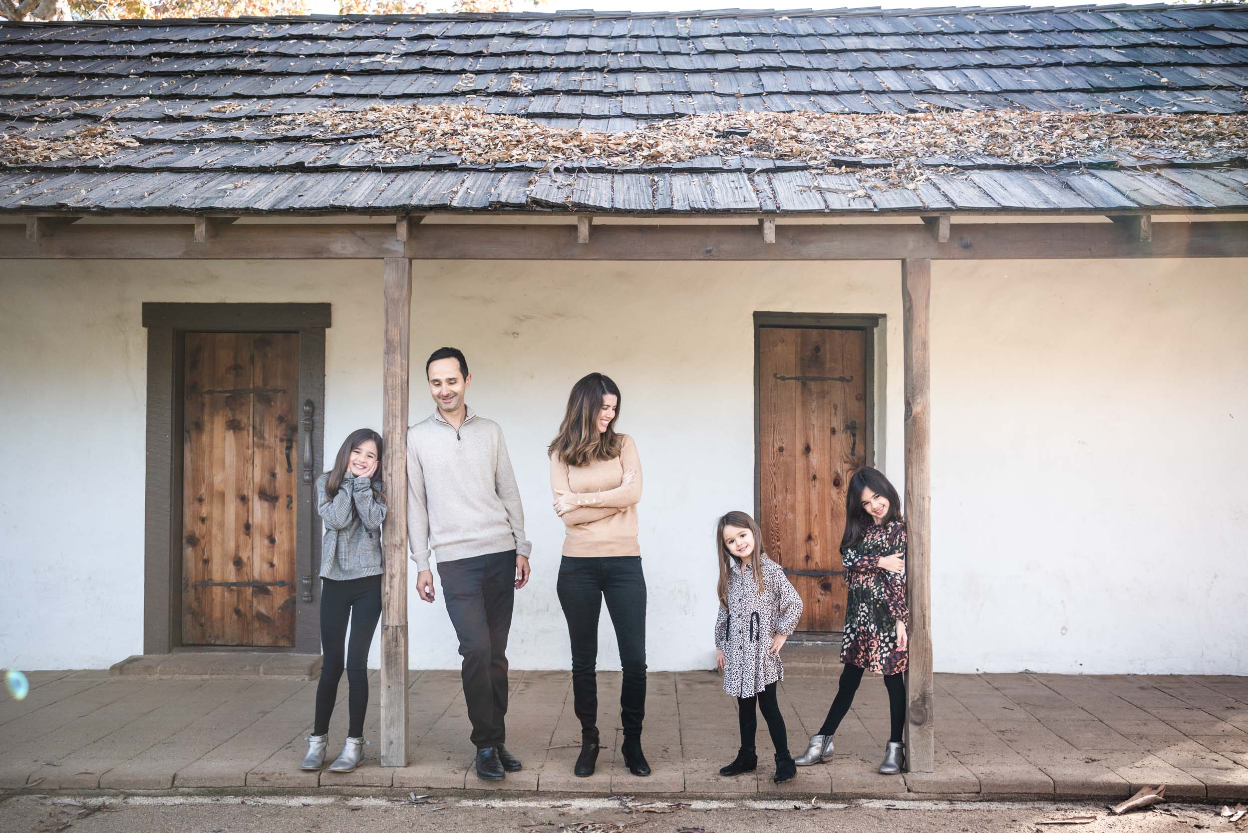 Lisa Hu Chen orange county family photographer family smiling in front of a white adobe house in san juan capistrano