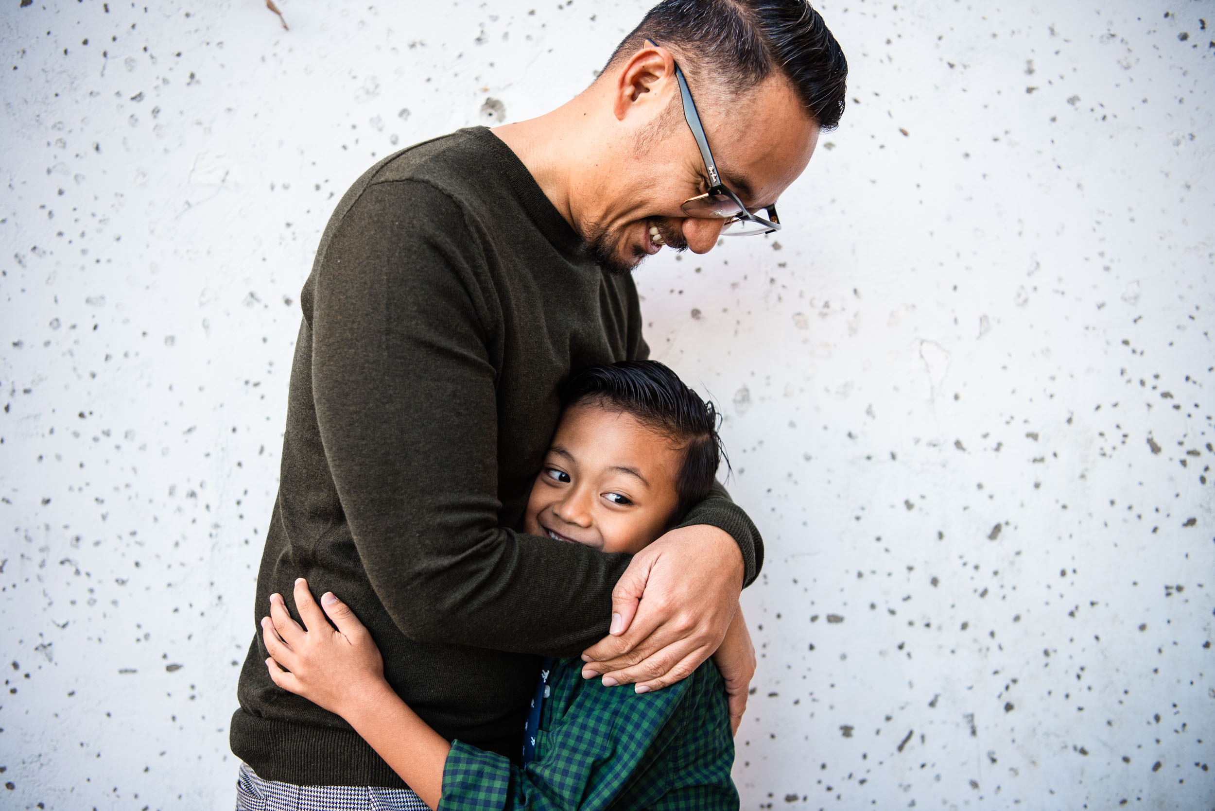 Lisa Hu Chen orange county family photographer | father and son hugging each other leaning against a building in Old Town Orange