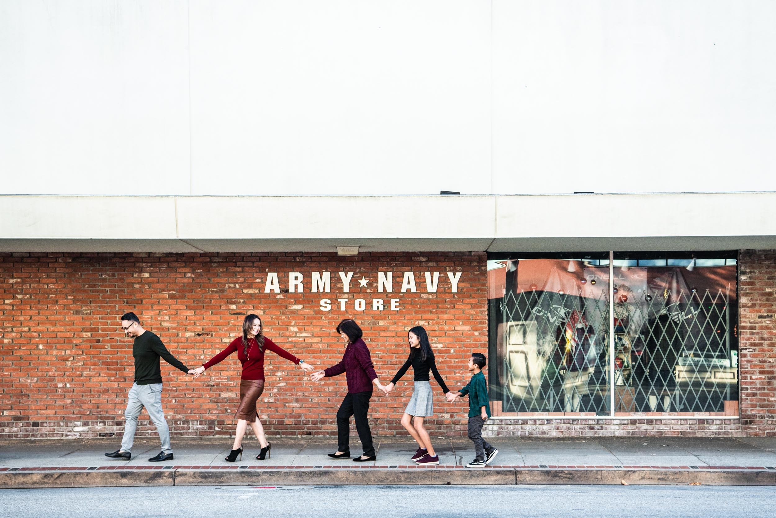 Lisa Hu Chen orange county family photographer | family holding hands looking at each other walking in front of the Army-Navy Store in Old Town Orange
