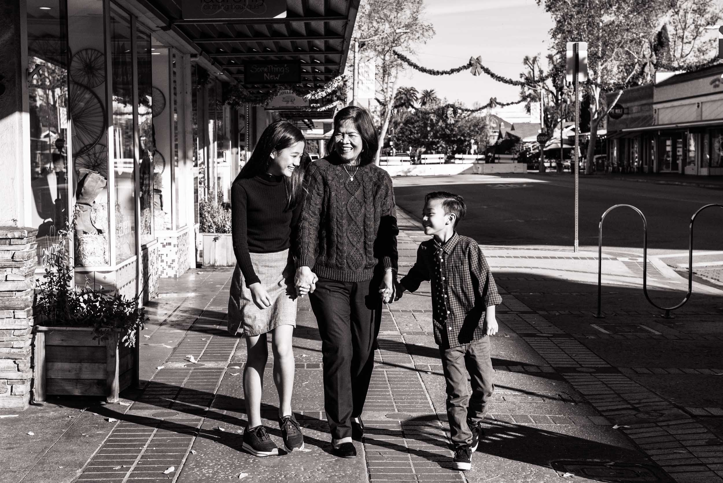 Lisa Hu Chen | grandma and her grandkids laughing, holding hands, and walking down the sidewalk in Old Town Orange